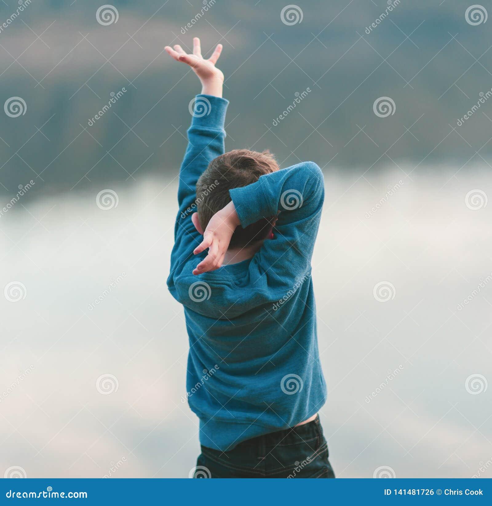 Een kleine jongen danst tegen een rivierachtergrond