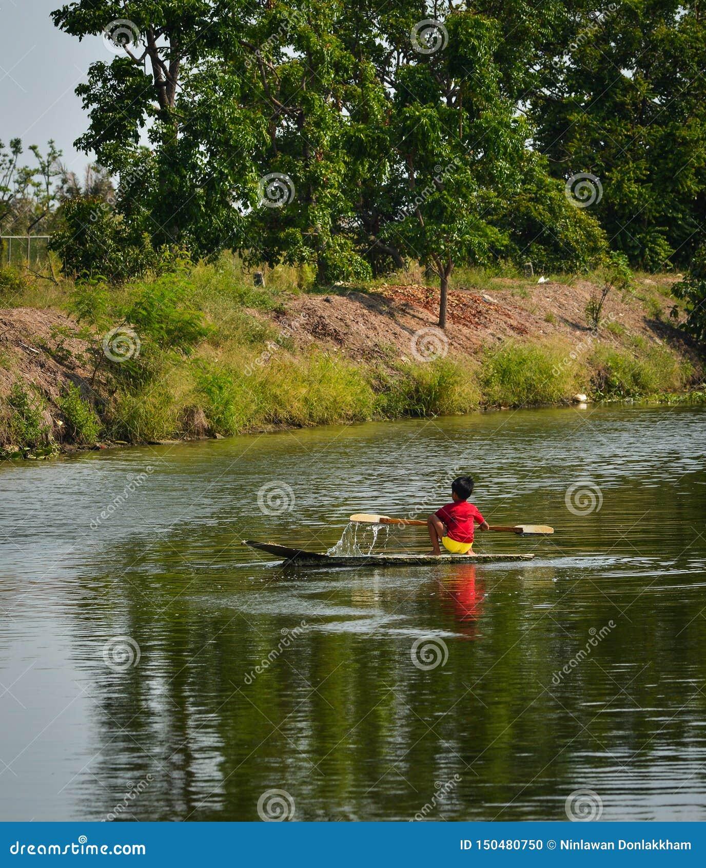 Een kleine jongen die houten boot op kanaal roeien