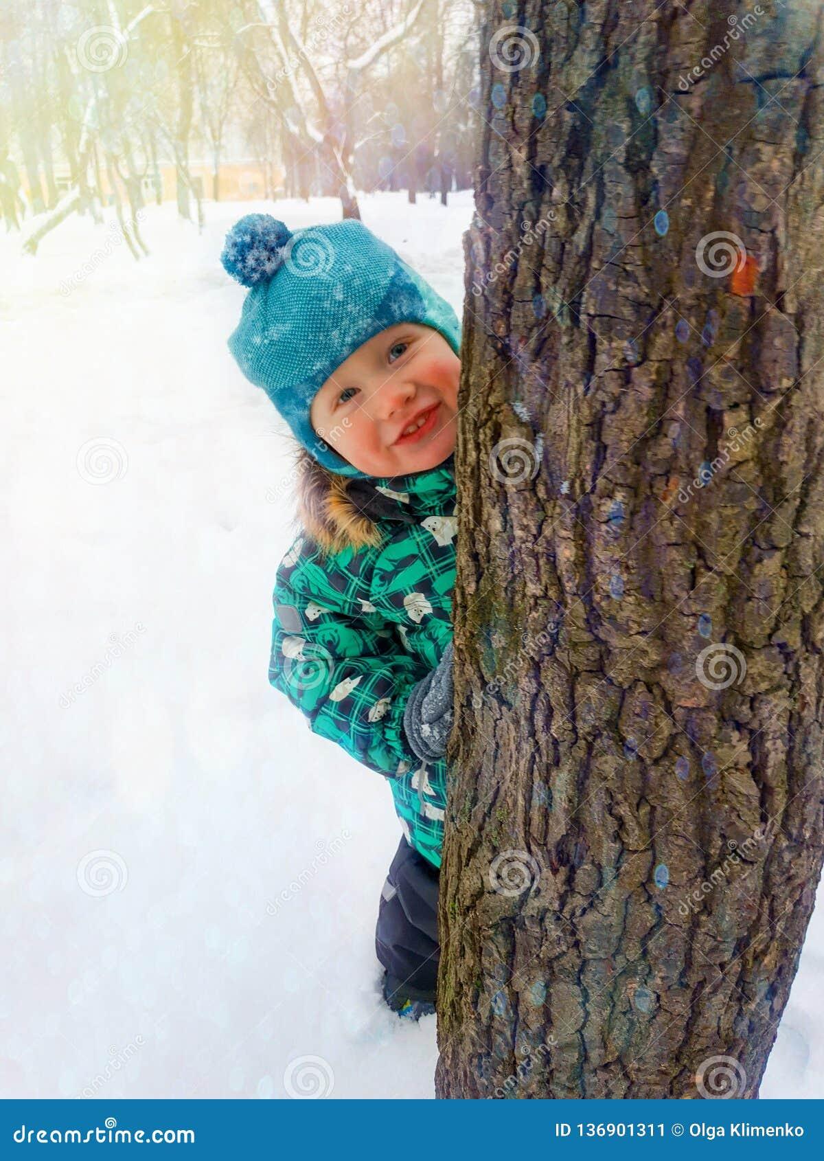 Een kleine jongen glimlacht gelukkig het gluren van achter een boomboomstam op een de winterdag