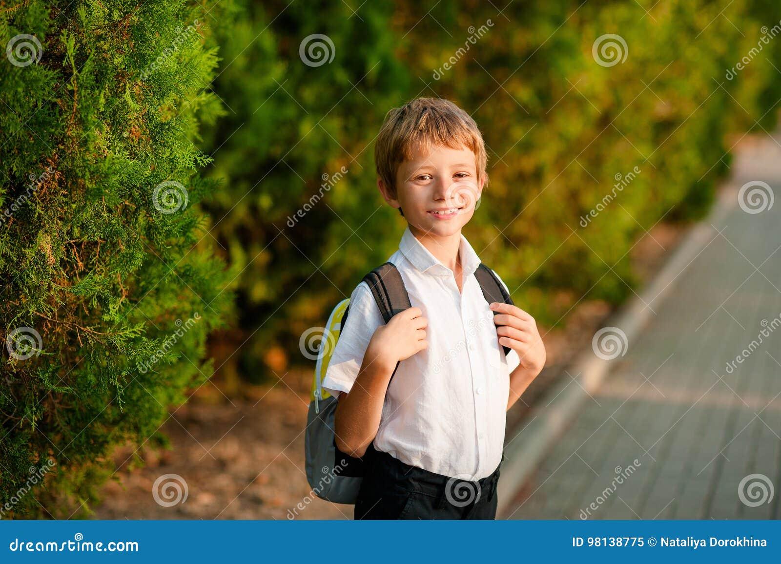 Een kleine jongen met een rugzak gaat op zijn manier naar school