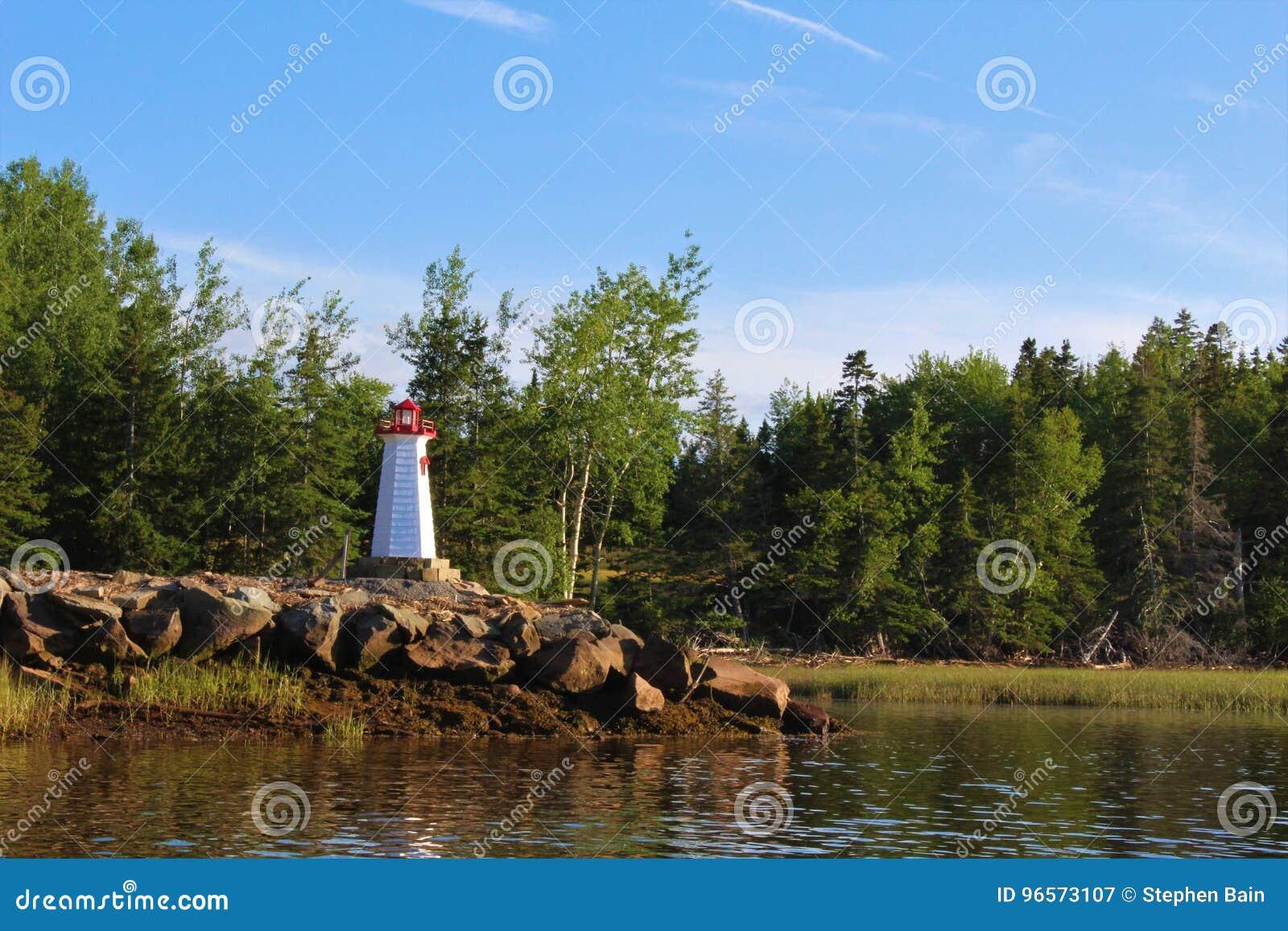 Een kleine modelvuurtoren op de kust van de Wallace-rivier in Nova Scotia op een de zomeravond
