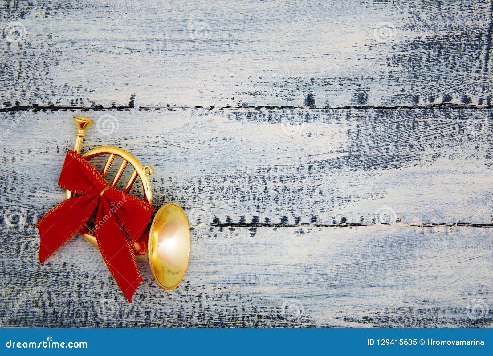Een kleine trompet, een hoorn met een rode boog op een versleten blauwe houten achtergrond De decoratie van Kerstmis