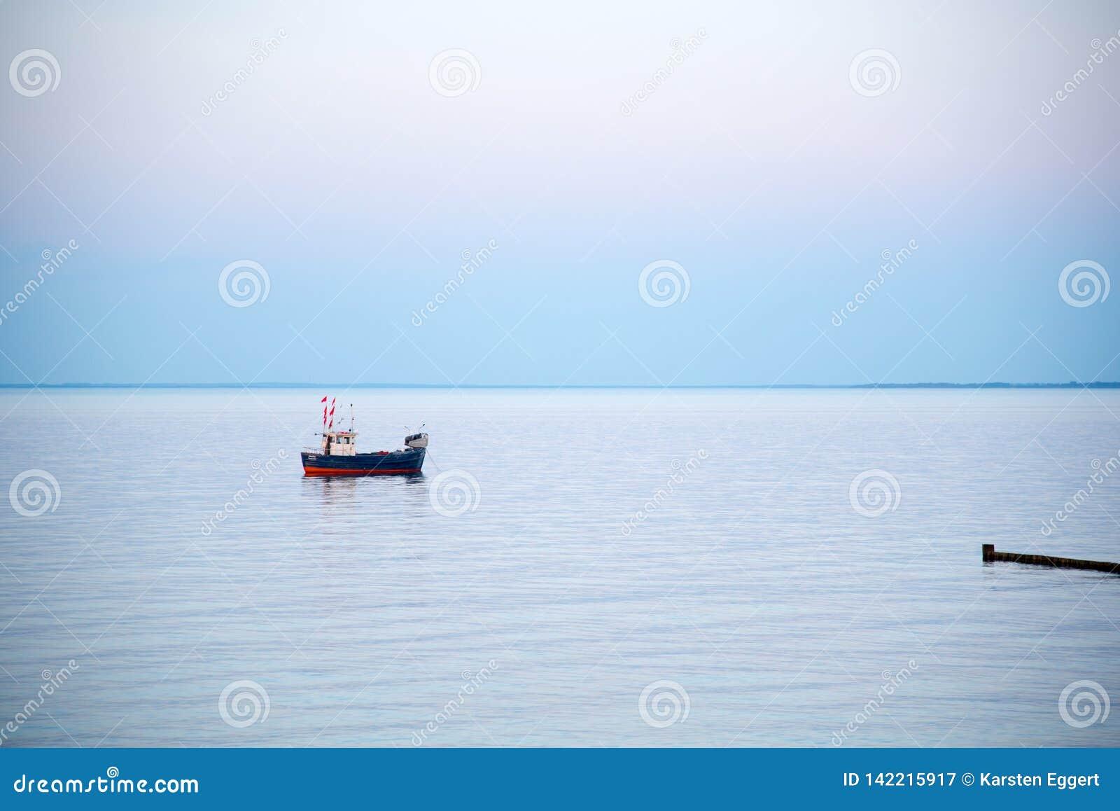 Een kleine vissersboot op het overzees in de vroege ochtend