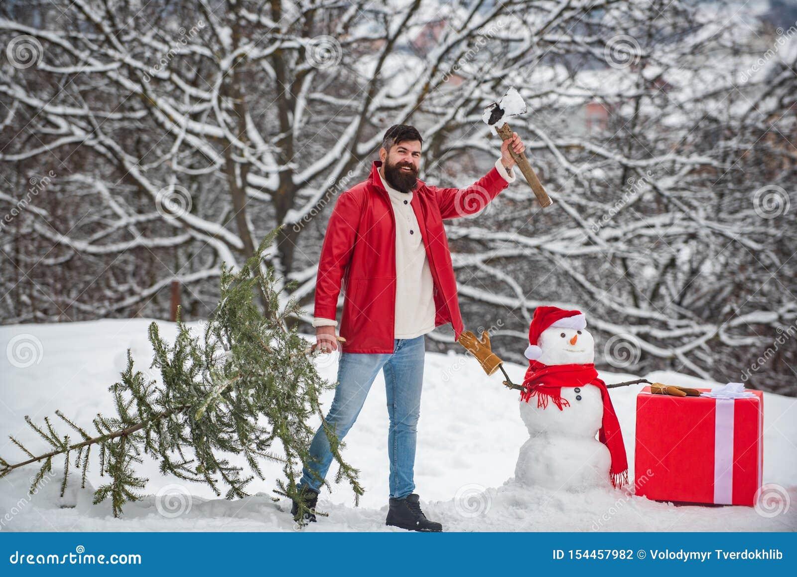 Een knappe jonge mens met de sneeuwmens draagt een Kerstboom Vrolijke Kerstmis en Gelukkige de groetkaart van het Nieuwjaar Sneeu