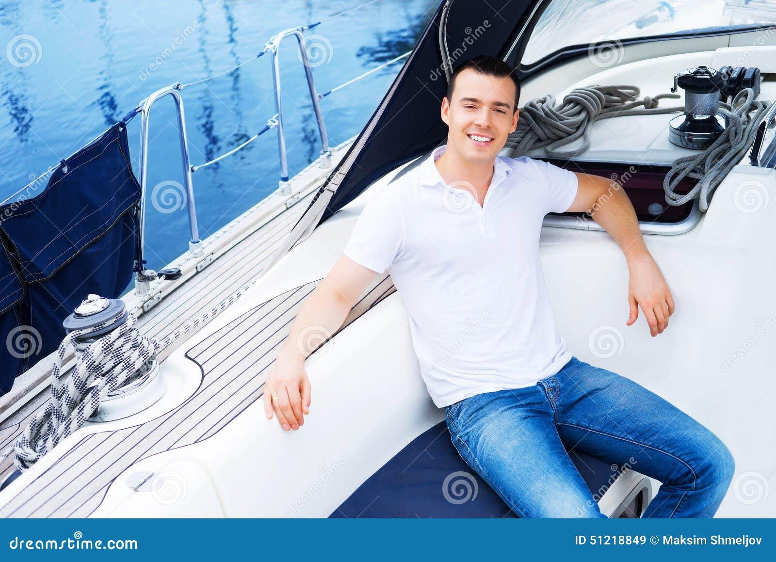 Een knappe mens die op een boot op het overzees ontspannen