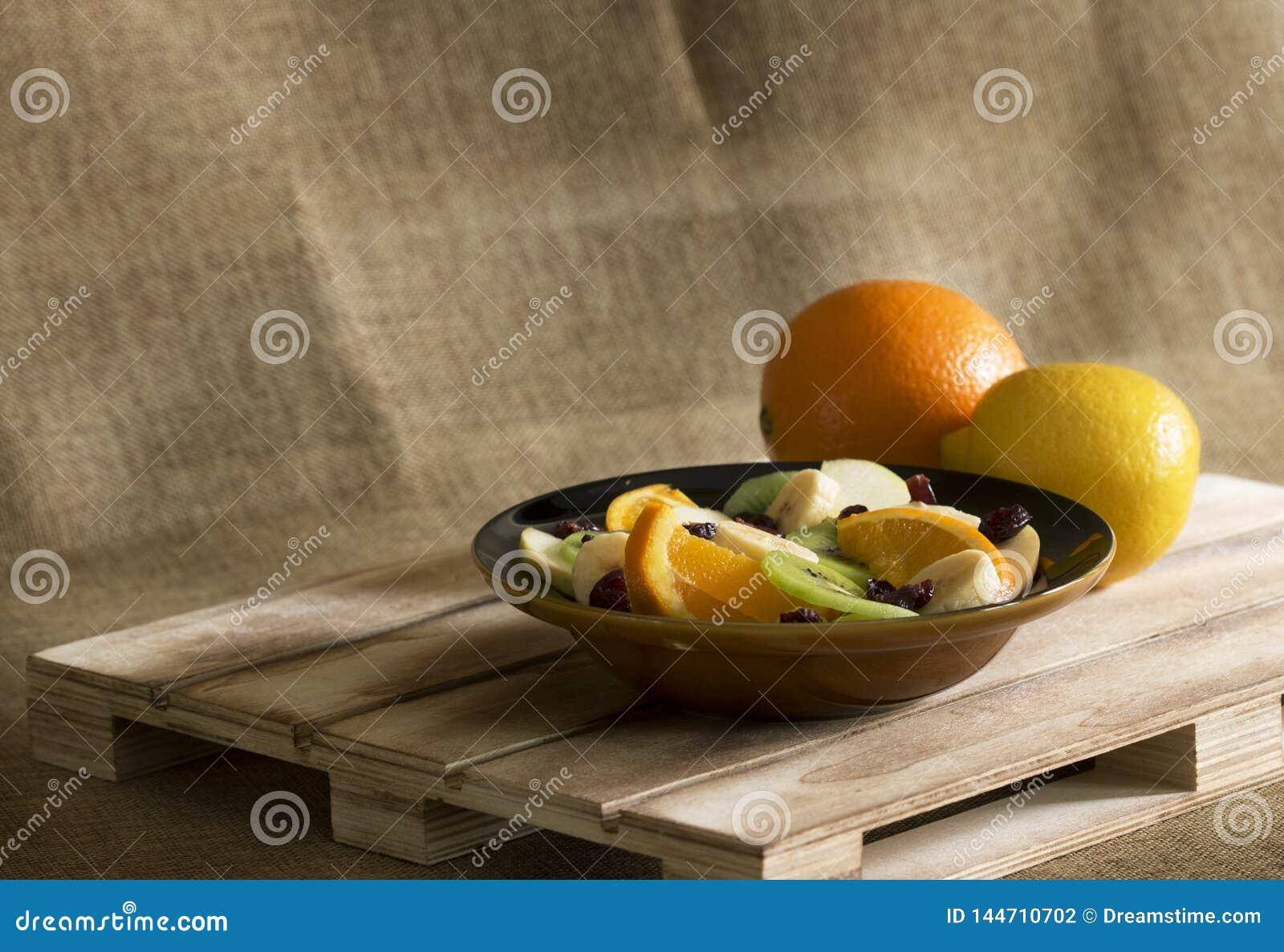Een kom fruitsalade met een sinaasappel en een citroen