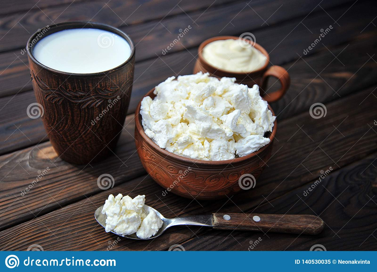 Een kom klei met kwark, een mok klei met zure room, een mok met melk en een lepel op een lijst