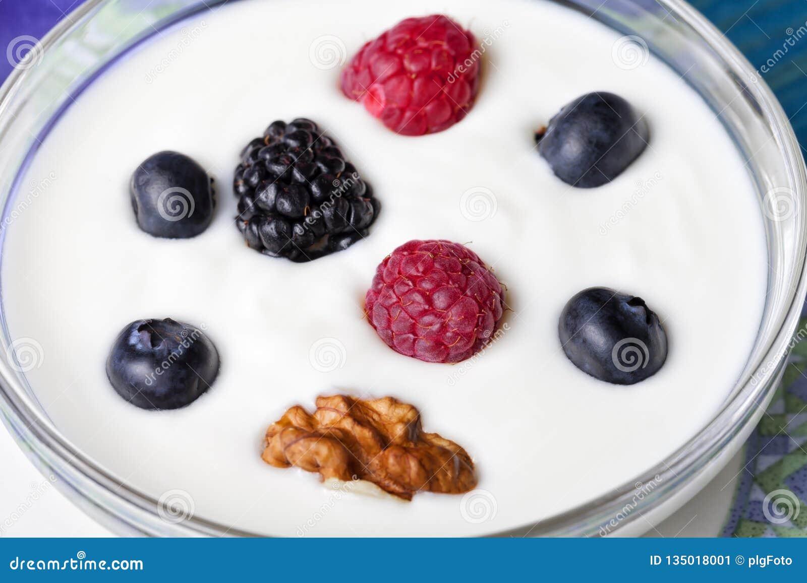 Een kom yoghurt met bosbessenredcurrants braambessen en okkernoten