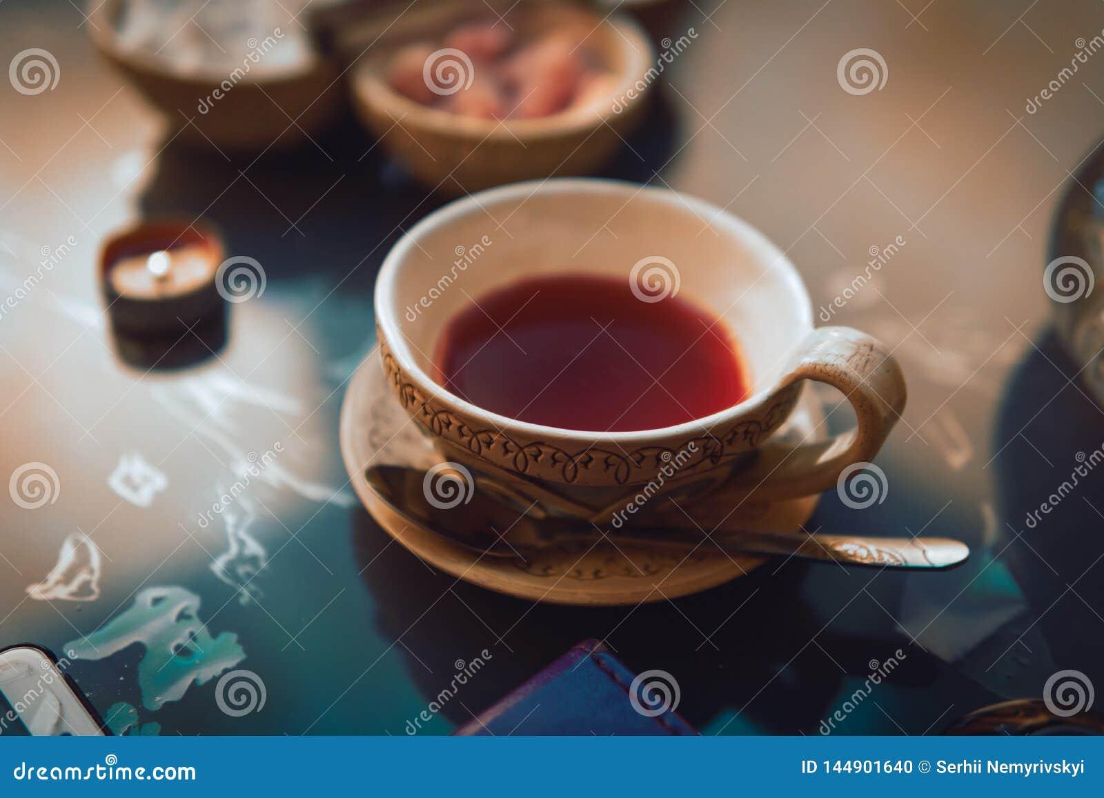 Een kop rode thee en suikerkubussen met verschillende smaken, met de hand gemaakt, op de glaslijst, oostelijke theeceremonie donk