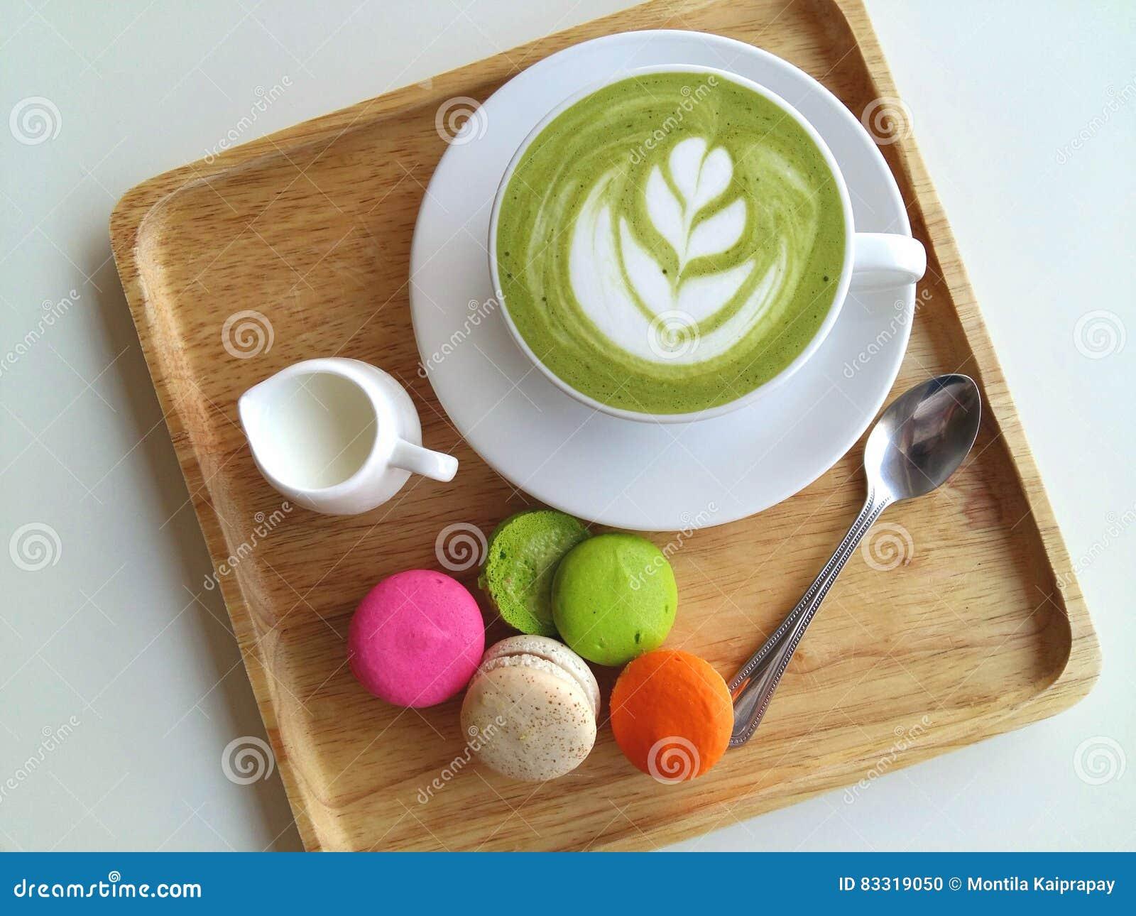 Een kop van hete matcha latte zo heerlijk met makaron op hout