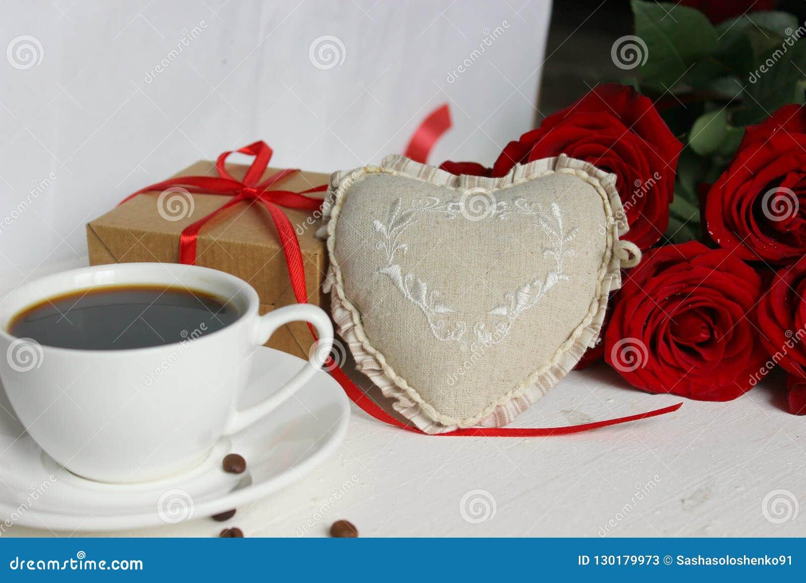 Een Kop van koffie, een boeket van rode rozen en een gift met een rood lint op het lijstclose-up