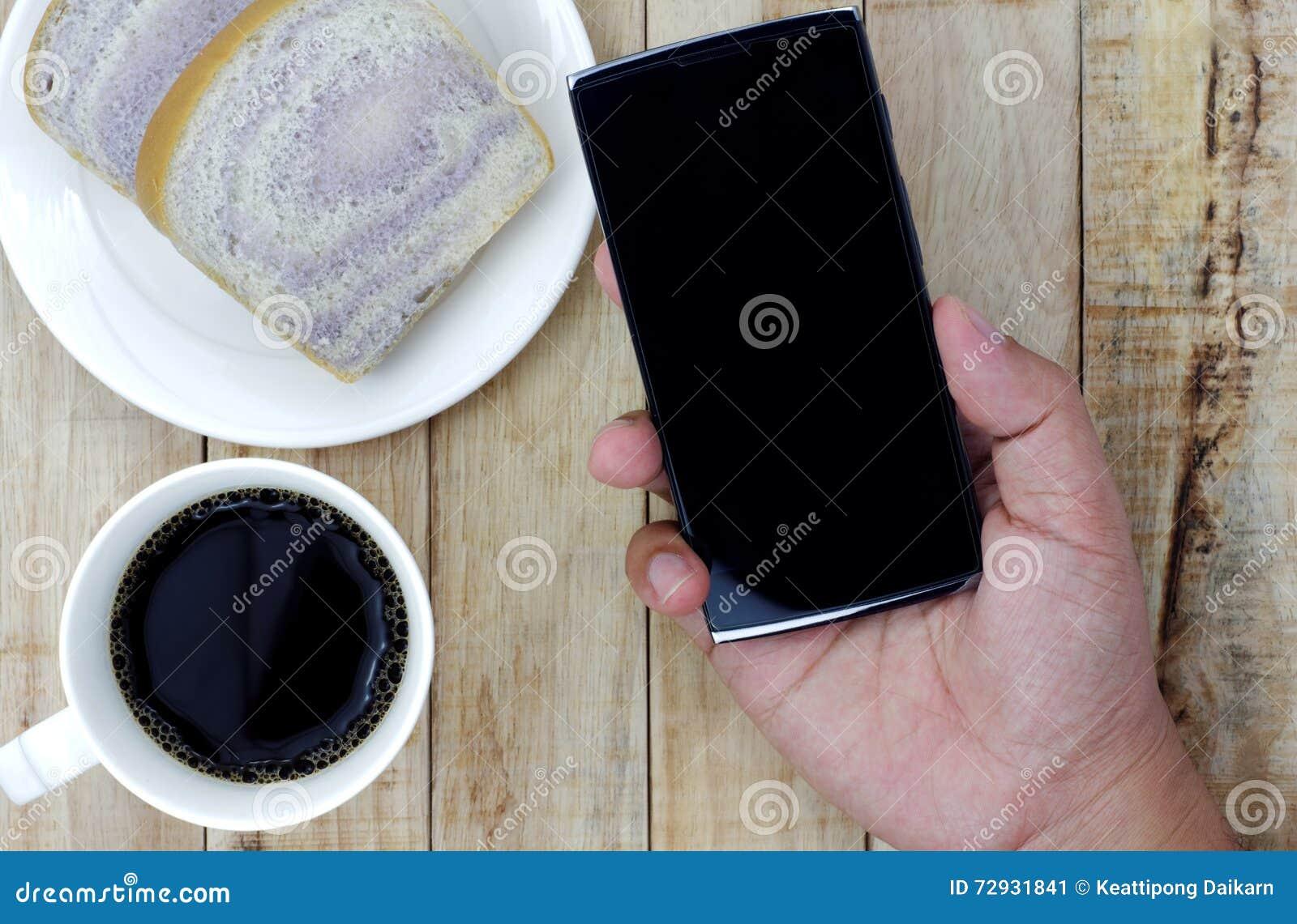 Een kop van koffie, brood op witte plaat, smartphone streeft ter beschikking na