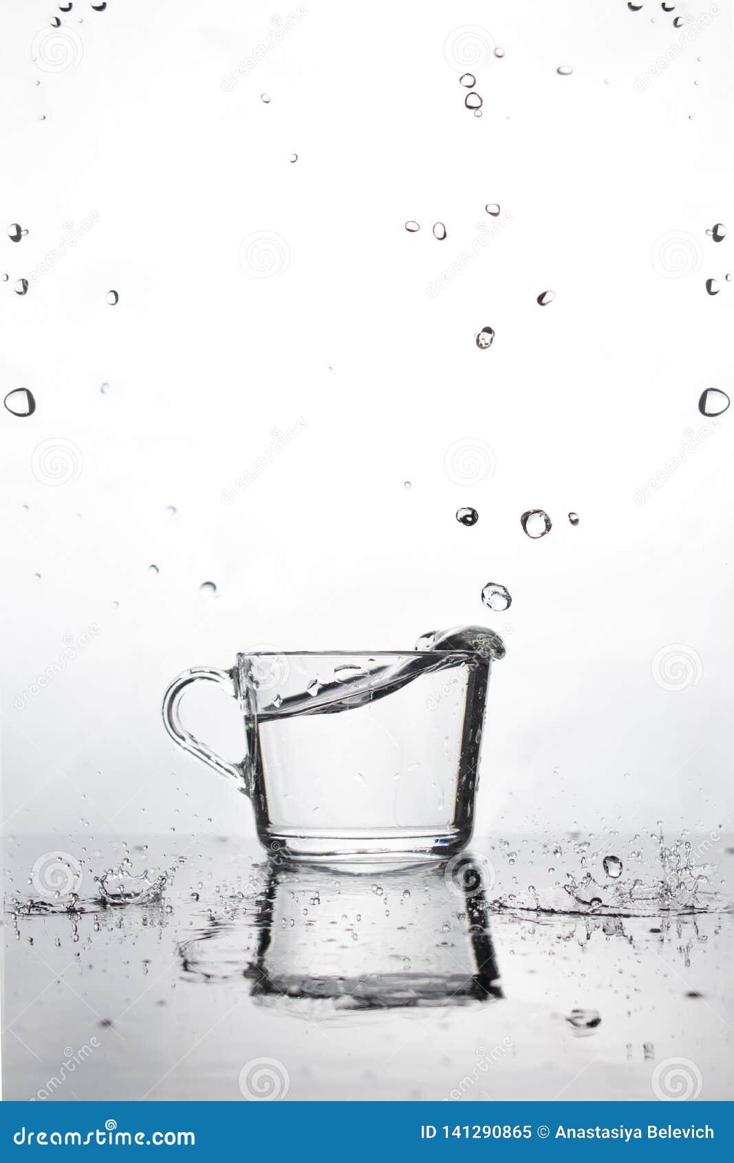 Een kop van water is op de natte lijst witte achtergrond met dalende waterdalingen Bezinning en kleine dalingen op een horizontal