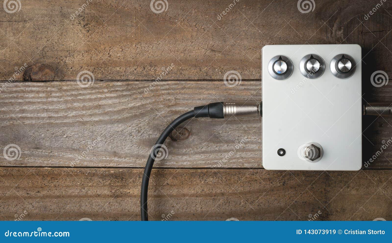 Een leeg wit gitaarpedaal met uitstekende knoppen en gestopte hefbomen op houten vloer