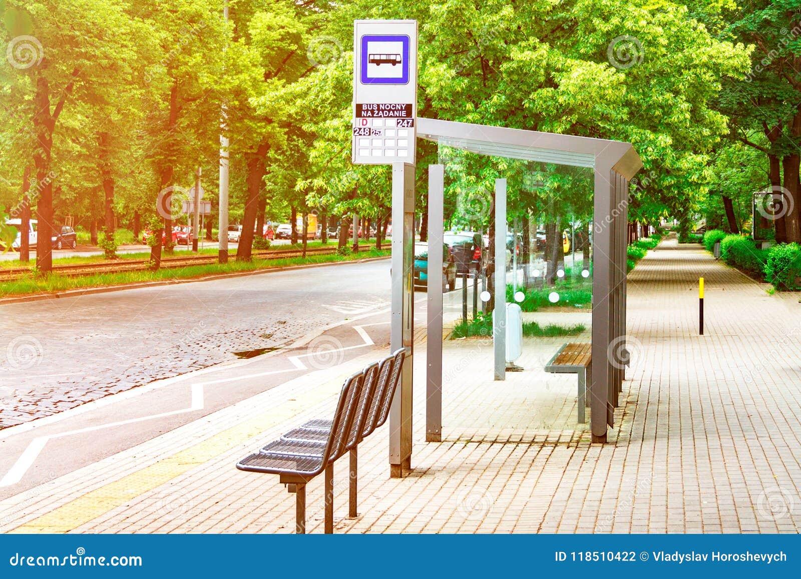 Een lege bushalte in het centrum van de stad wordt aangestoken door de zon, een einde tegen de achtergrond van groene bomen