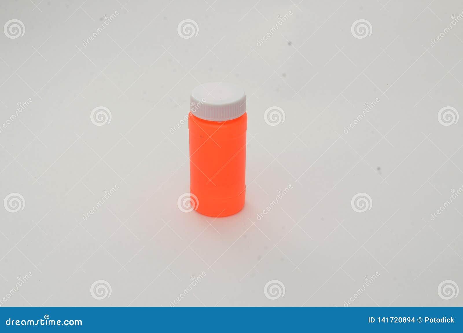 Een lege oranje fles met een wit deksel op een duidelijk wit