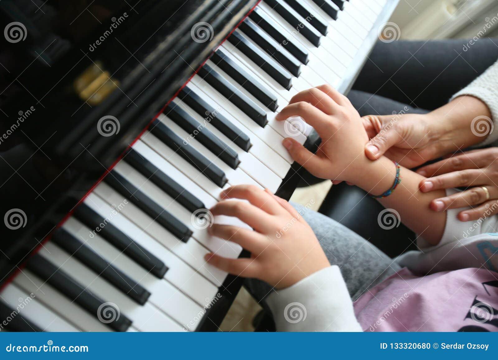 Een leraar onderwijst het spelen piano haar student
