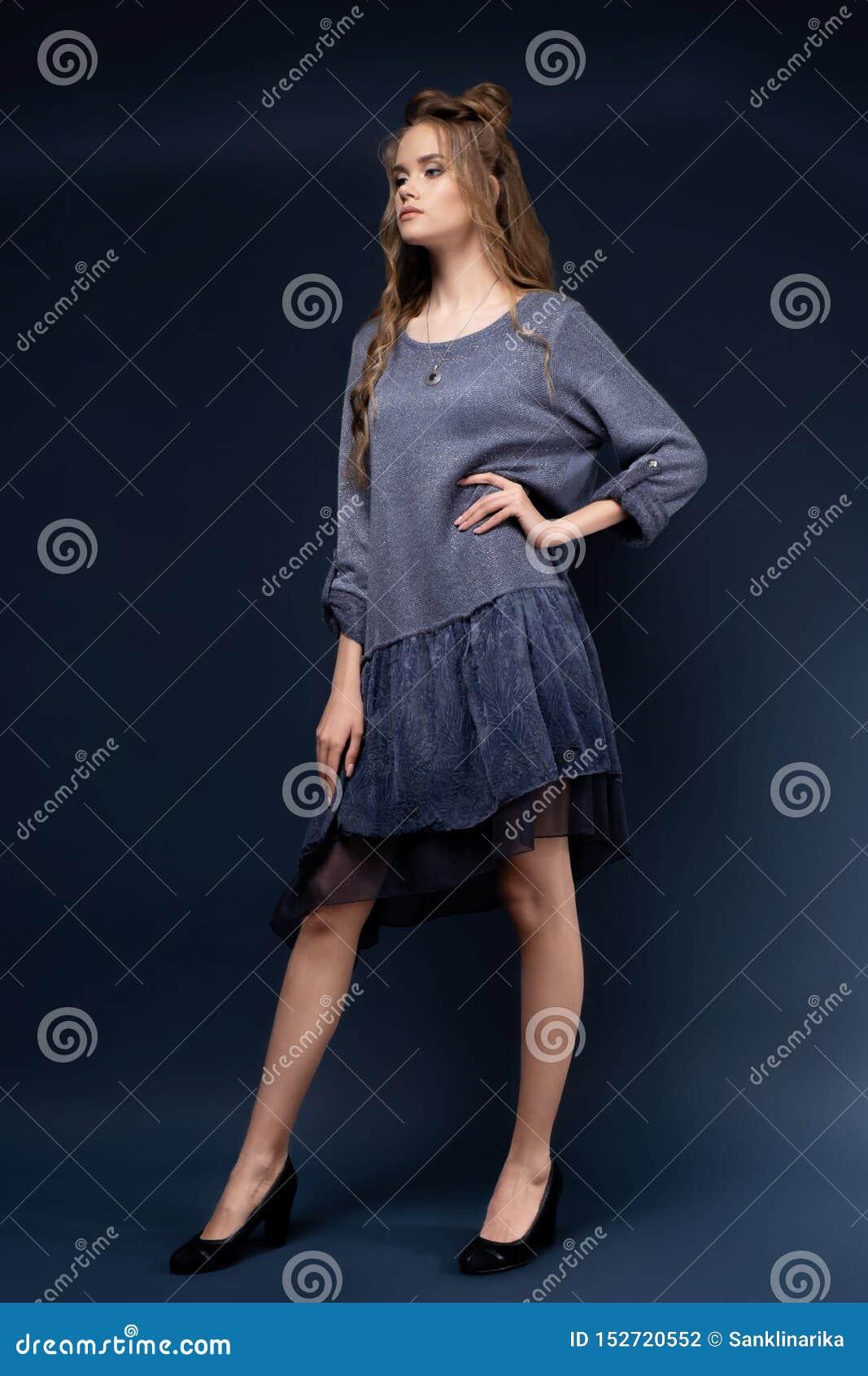 Een leuk jong meisje in een blauwe gebreide kleding op een blauwe achtergrond met een kapsel en een krullend lang haar