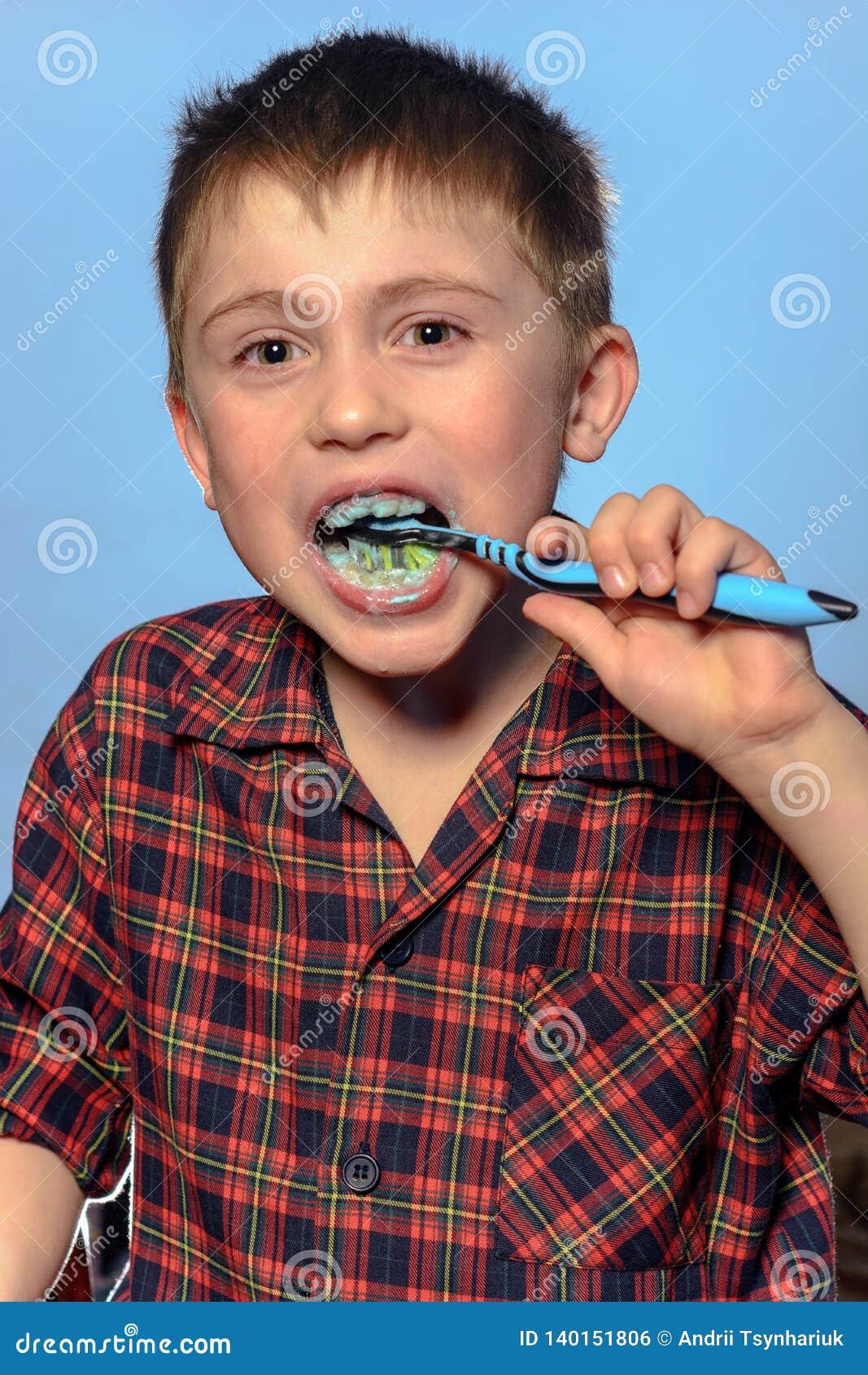 Een leuke jongen in pyjama s borstelt tanden met tandpasta vóór bedtijd op een blauwe achtergrond
