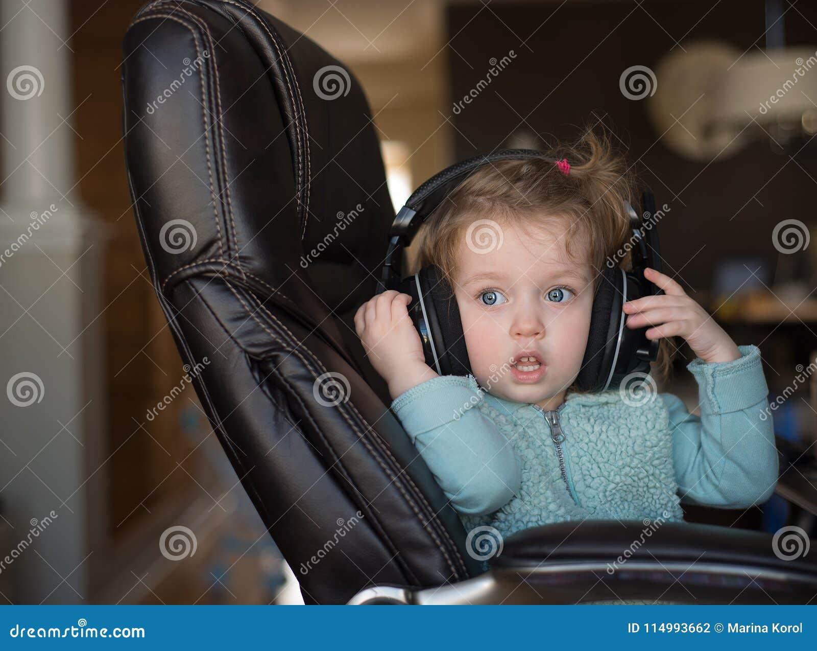 Een leuke kleine Kaukasische blondebaby met blauwe ogen met hoofdtelefoons zit op een stoel en kijkt vooruit