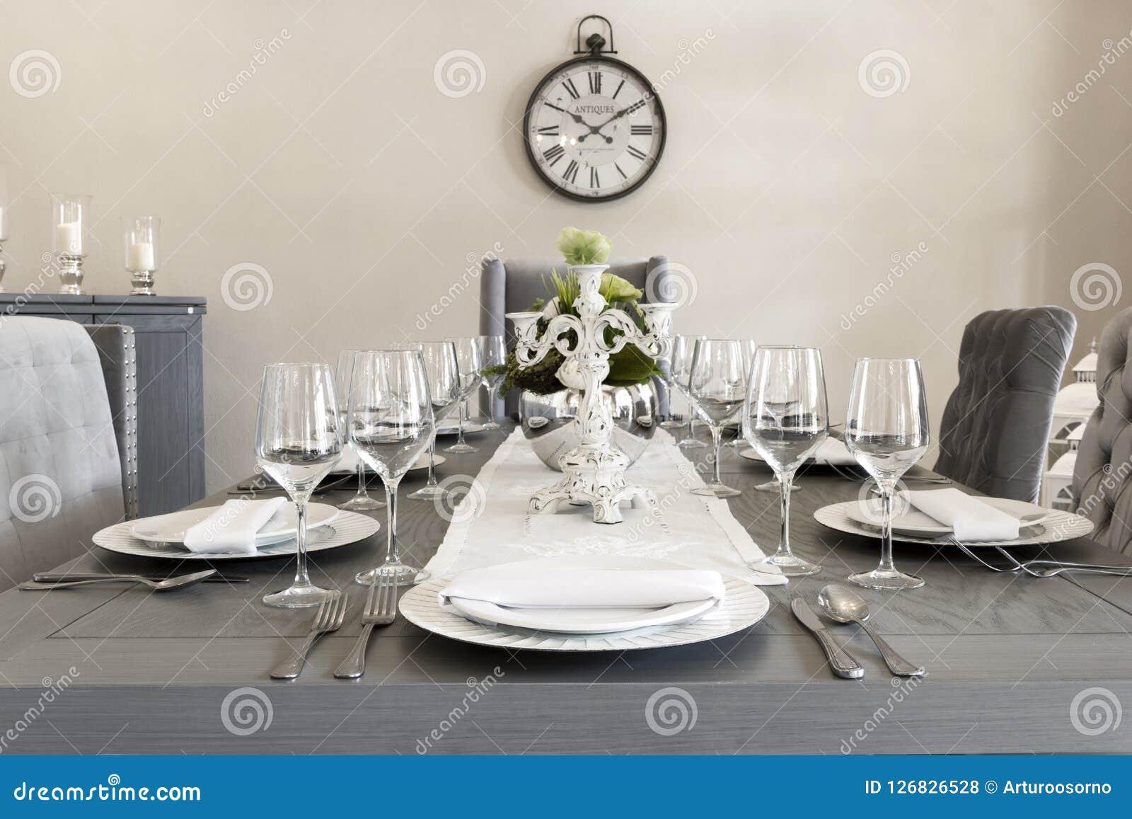 Een luxueuze eetkamer van een huis met glazen en platen