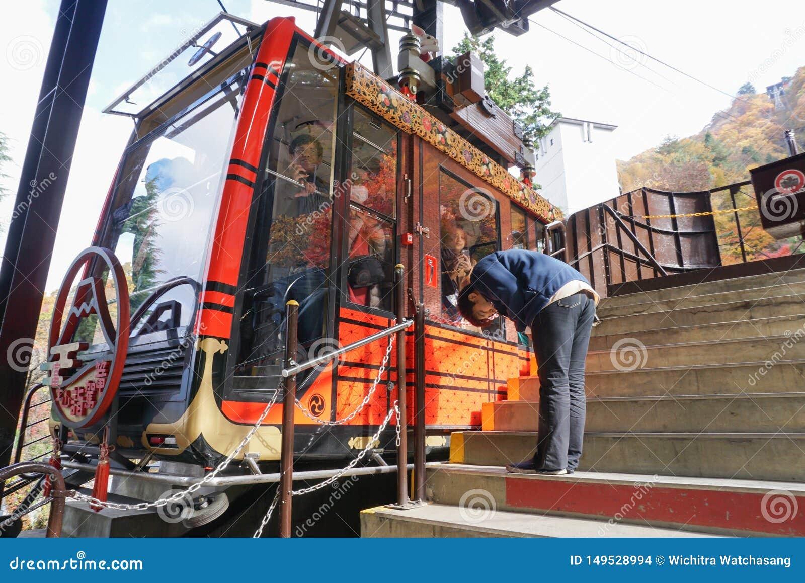 Een man stokvoering de reiziger van de kabelwagen na eind van de dienst bij het gezichtspunt van Meerkawaguchi, Japan