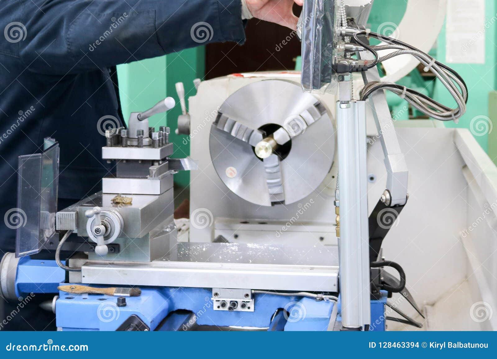 Een mannelijke arbeider werkt aan een grotere de slotenmakerdraaibank van het metaalijzer, materiaal voor reparaties, het metaalw