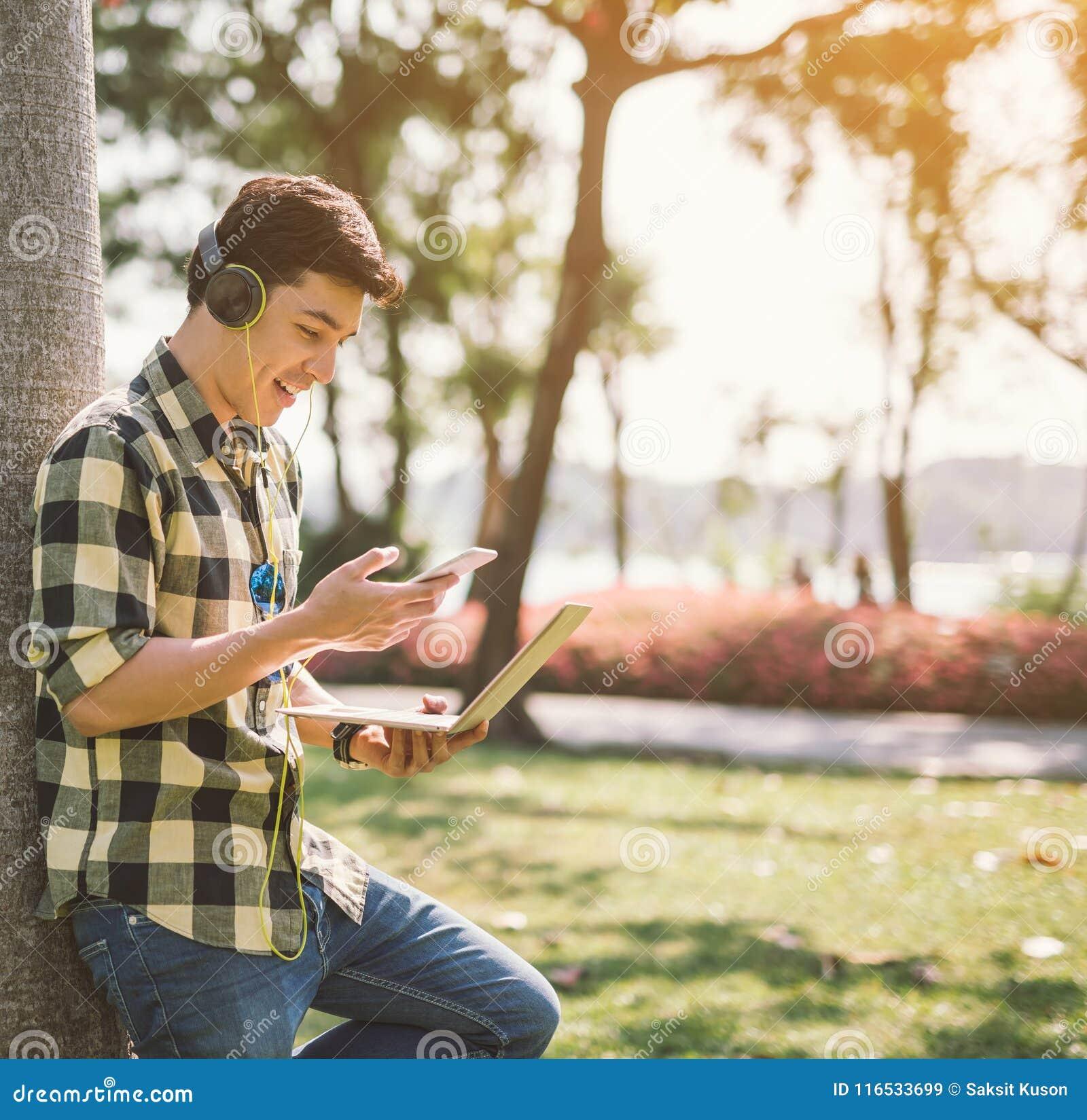 Een mannelijke student en het luisteren muziek die gezet op een gras in het stadspark ontspannen