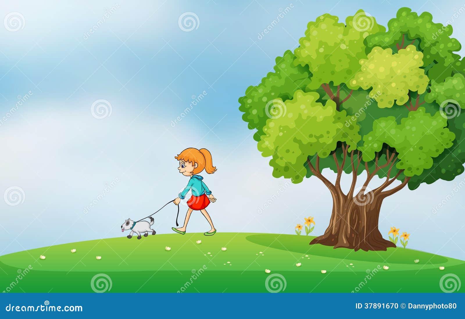 Een meisje die met haar hond bij de heuveltop lopen