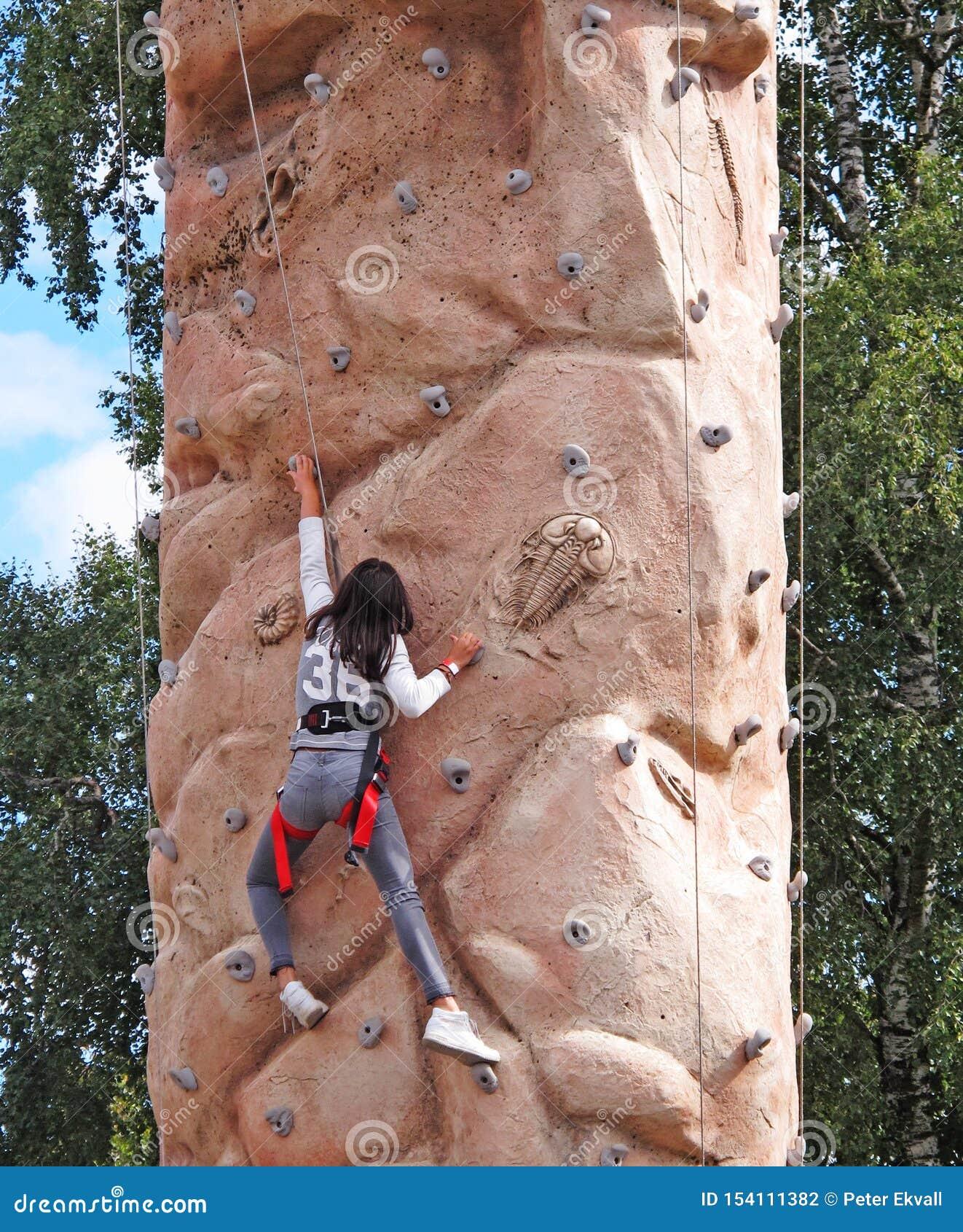 Een meisje die op muur met uitrusting beklimmen