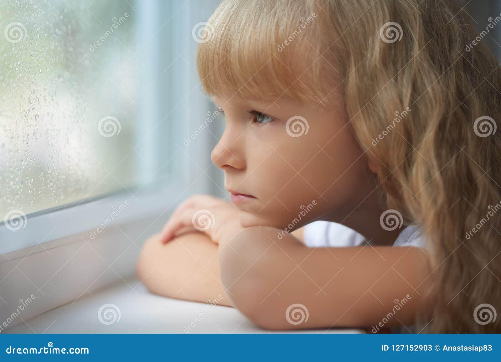 Een meisje die uit het venster op een regenachtige dag kijken