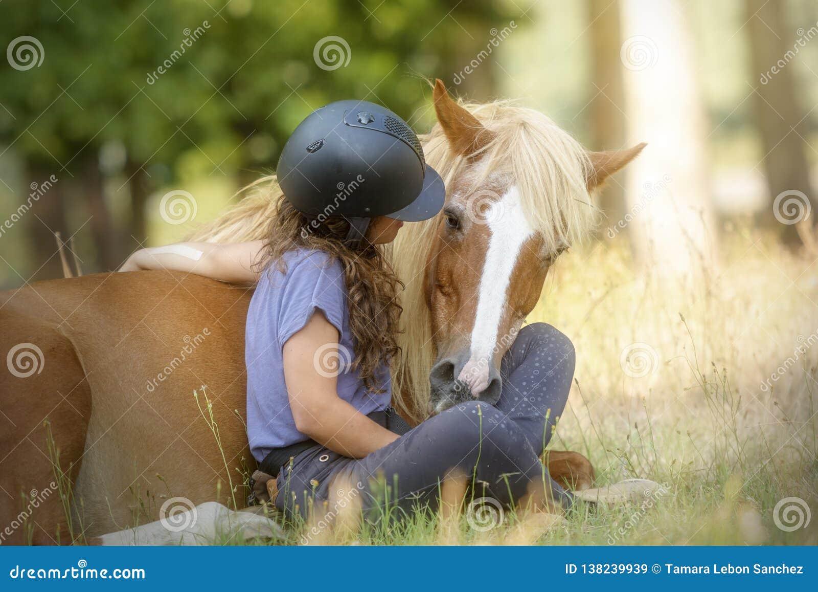 Een meisje en haar mooie zuringsponey die trucs tonen die met natuurlijke dressuur worden geleerd