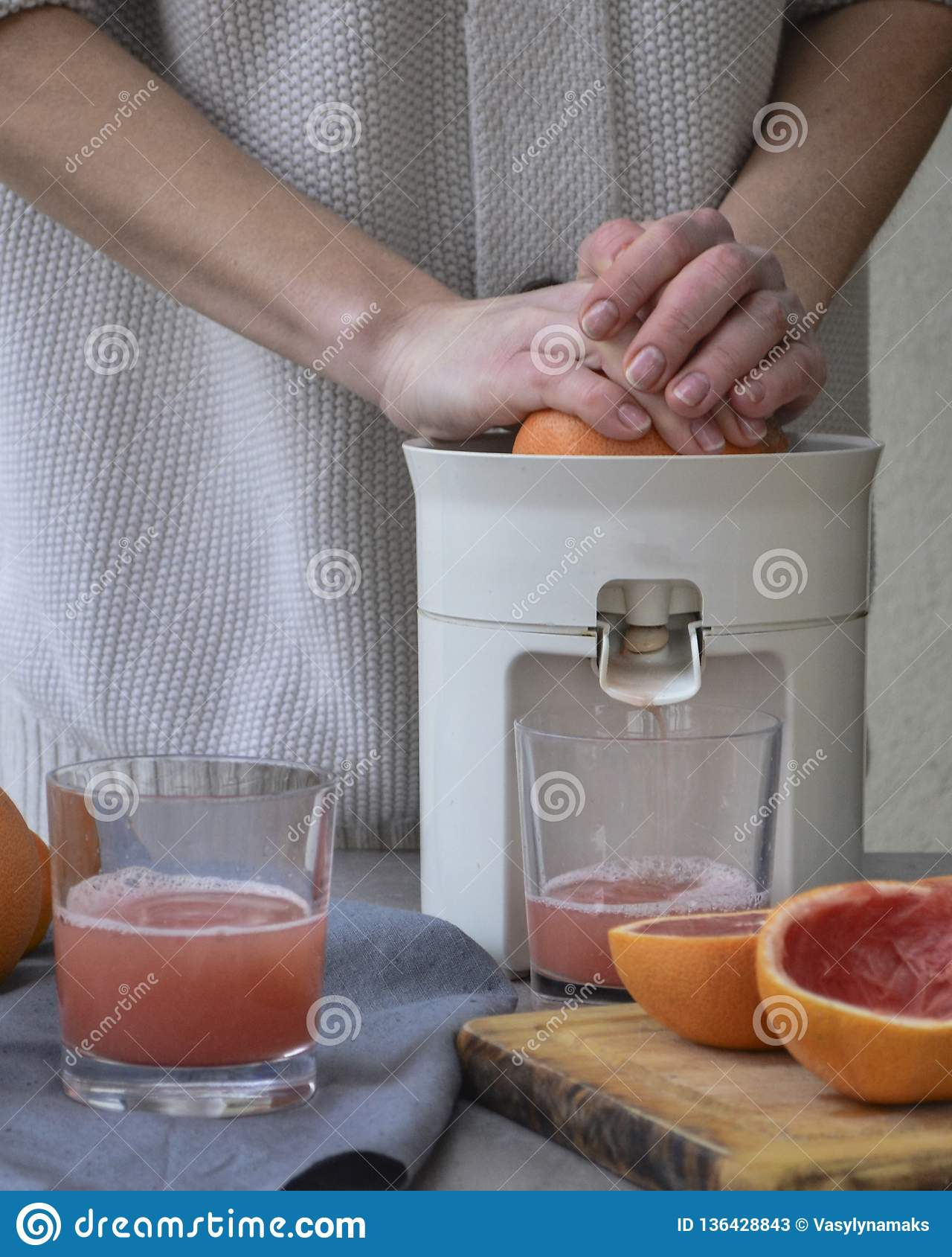 Een meisje maakt verse grapefruit juice