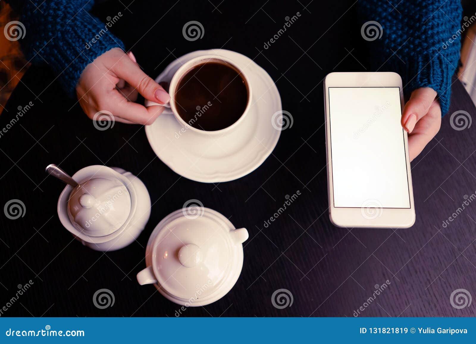 Een meisje met koffie en smartphone