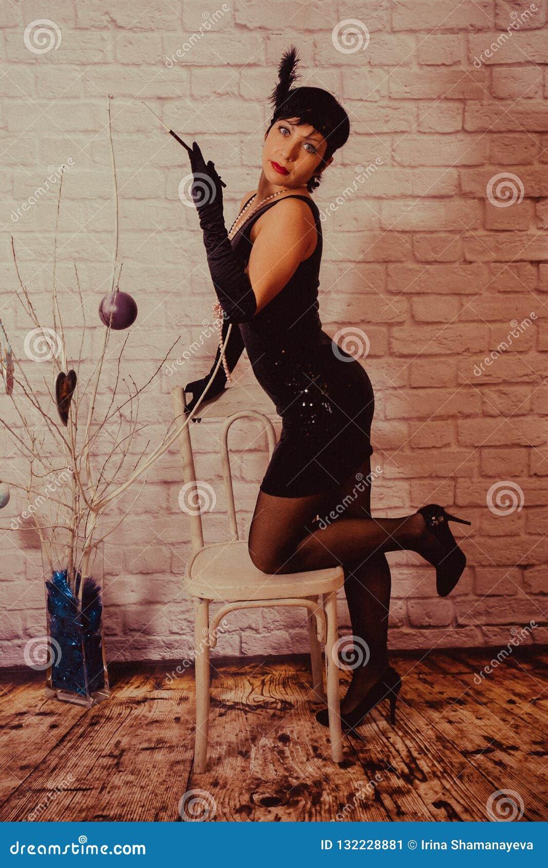 Een meisje met kort zwart haar met een verband met lovertjes en veren op haar hoofd in een kleding met lovertjes in Chicago