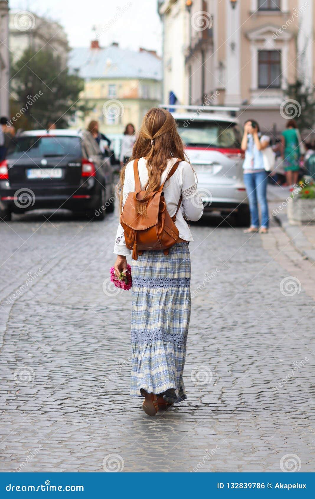 Een meisje met lang, los haar loopt in de mooie kleren van de hippiestijl langs de oude straten van een middeleeuwse stad Jonge t