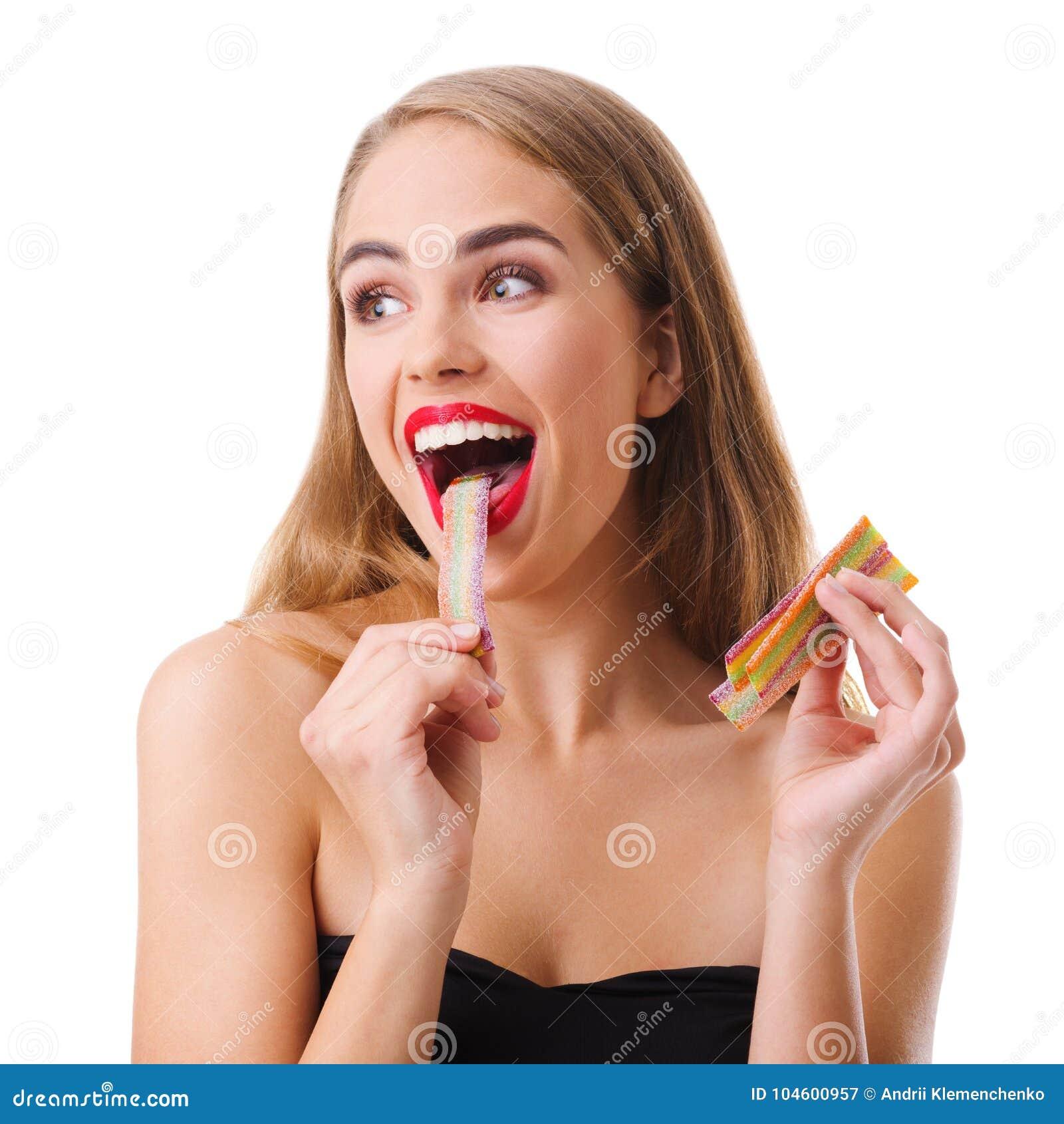Een meisje met rode lippen opende wijd haar mond en eet een bar van het geleisuikergoed Geïsoleerdj op witte achtergrond