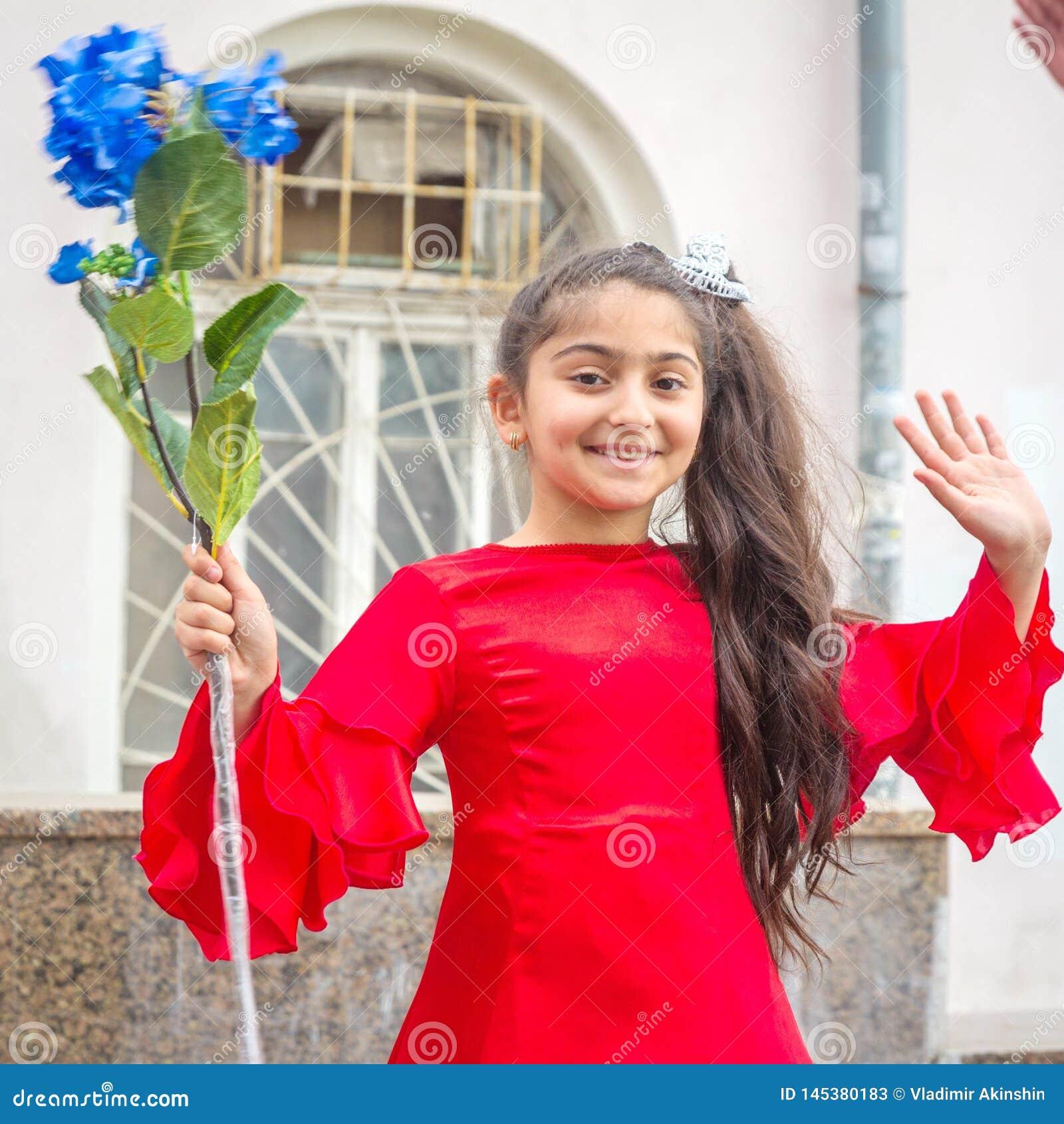 Een meisje in een mooie kleding bij een feestelijke optocht van gediplomeerden van scholen
