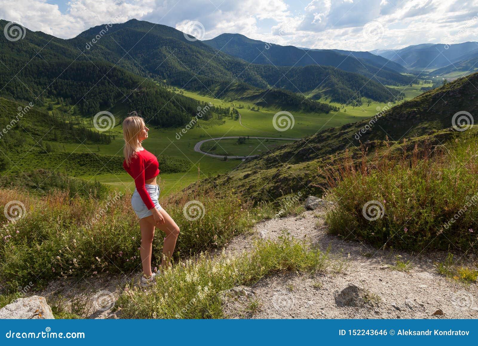Een meisje in een rode bovenkant en de blauwe borrels op de rand van een klip in de Altai-Bergen, hieronder zijn groene gebieden