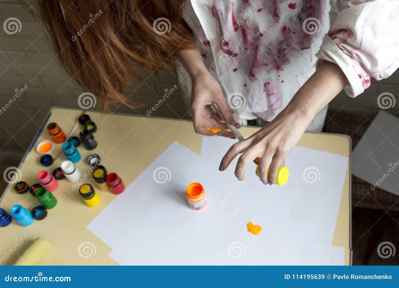 Een meisje schildert beeld met kleuren gebruikend haar eigen handen