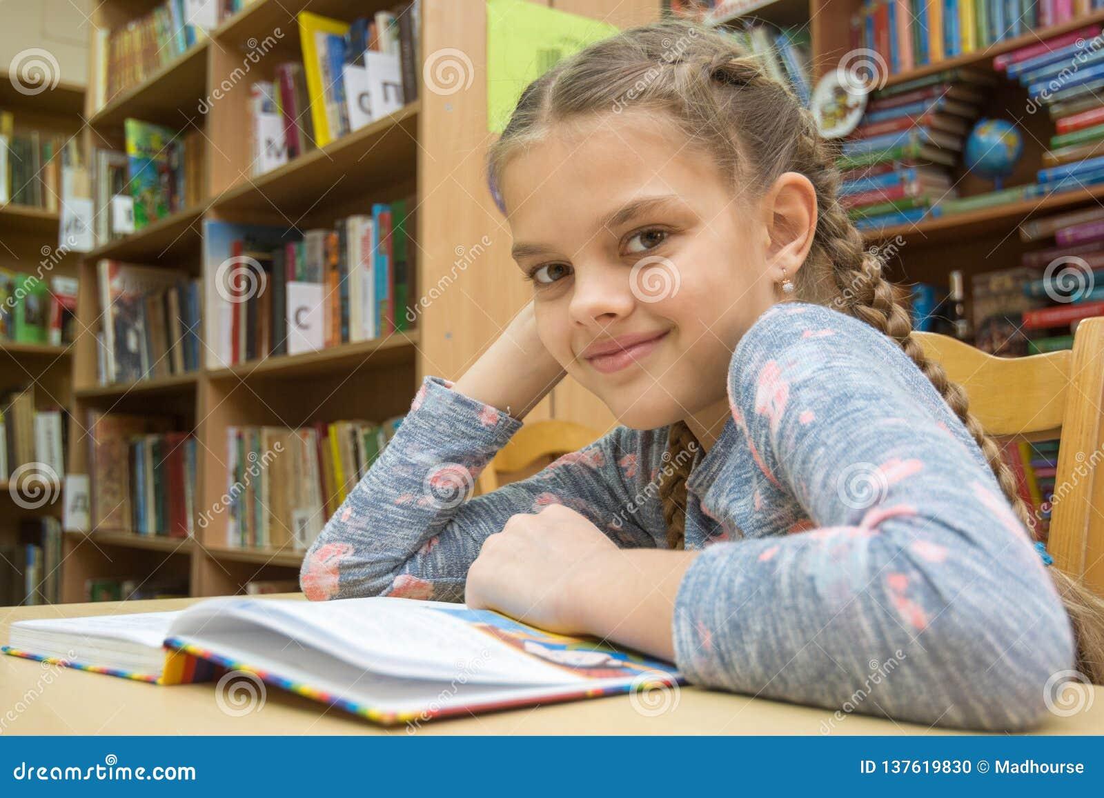 Een meisje van tien jaar brengt tijd in de bibliotheek door