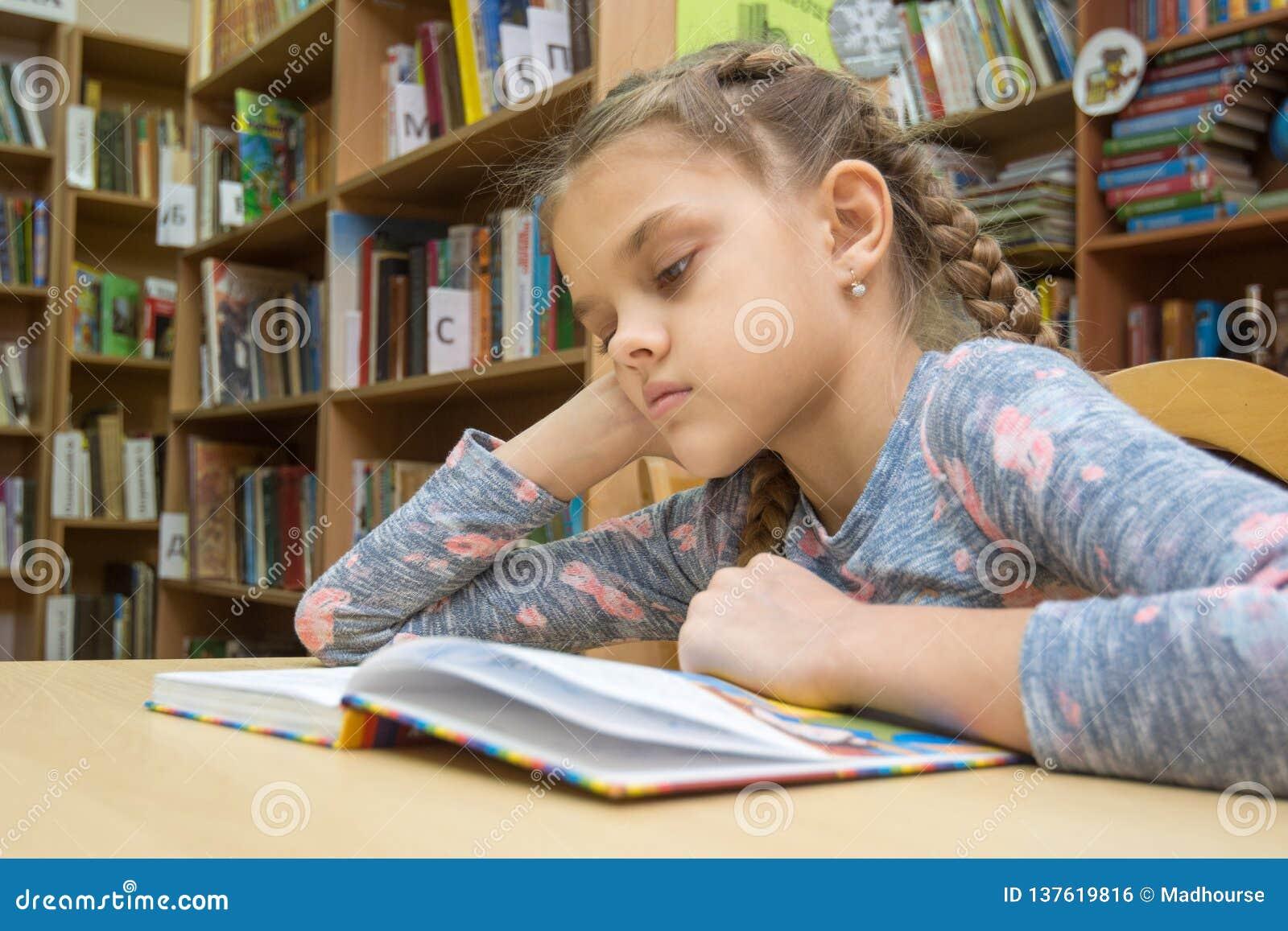 Een meisje van tien jaar oud leest een boek in de lezingsruimte