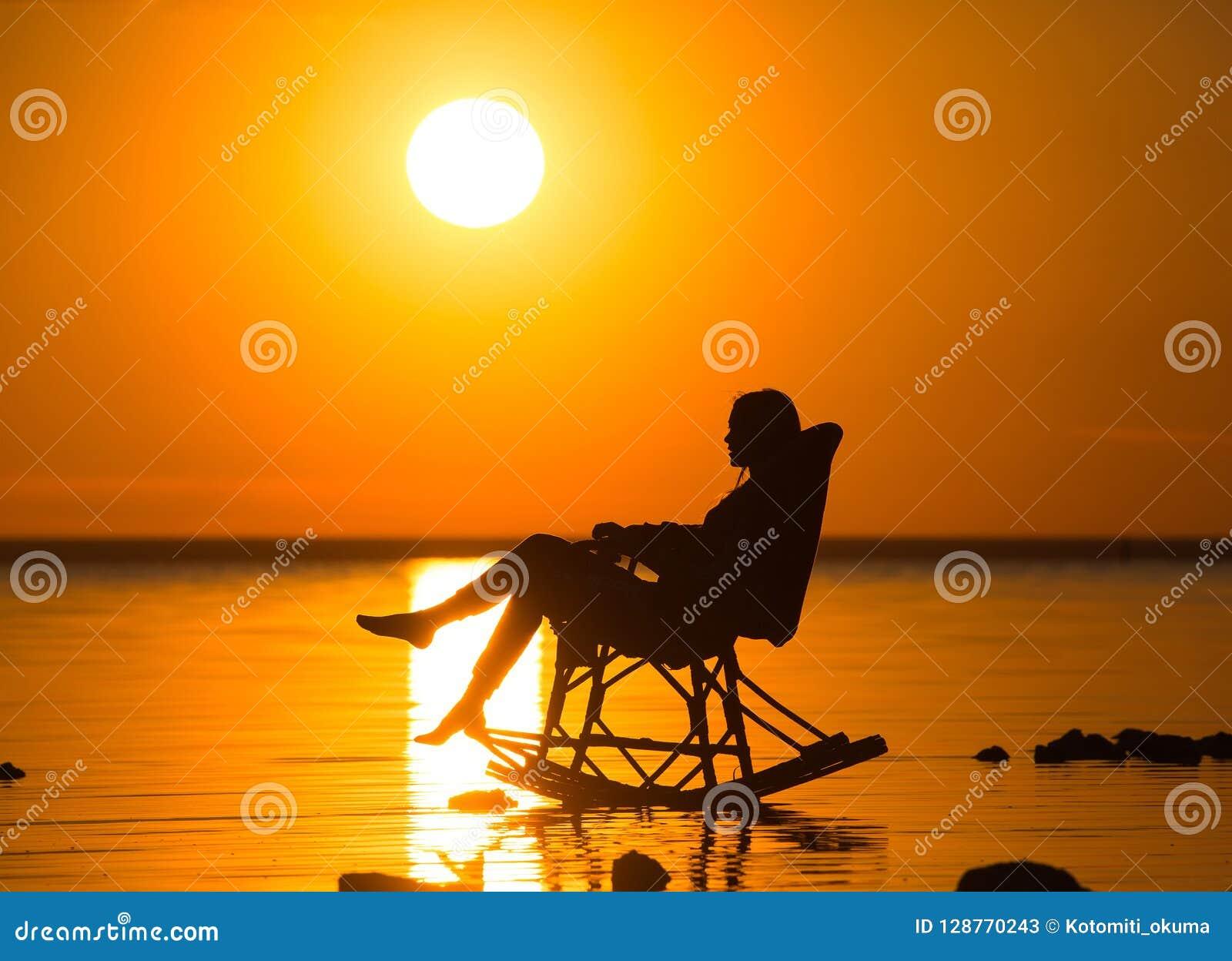 Een meisjeszitting in een rieten schommelstoel tegen de zonsondergang