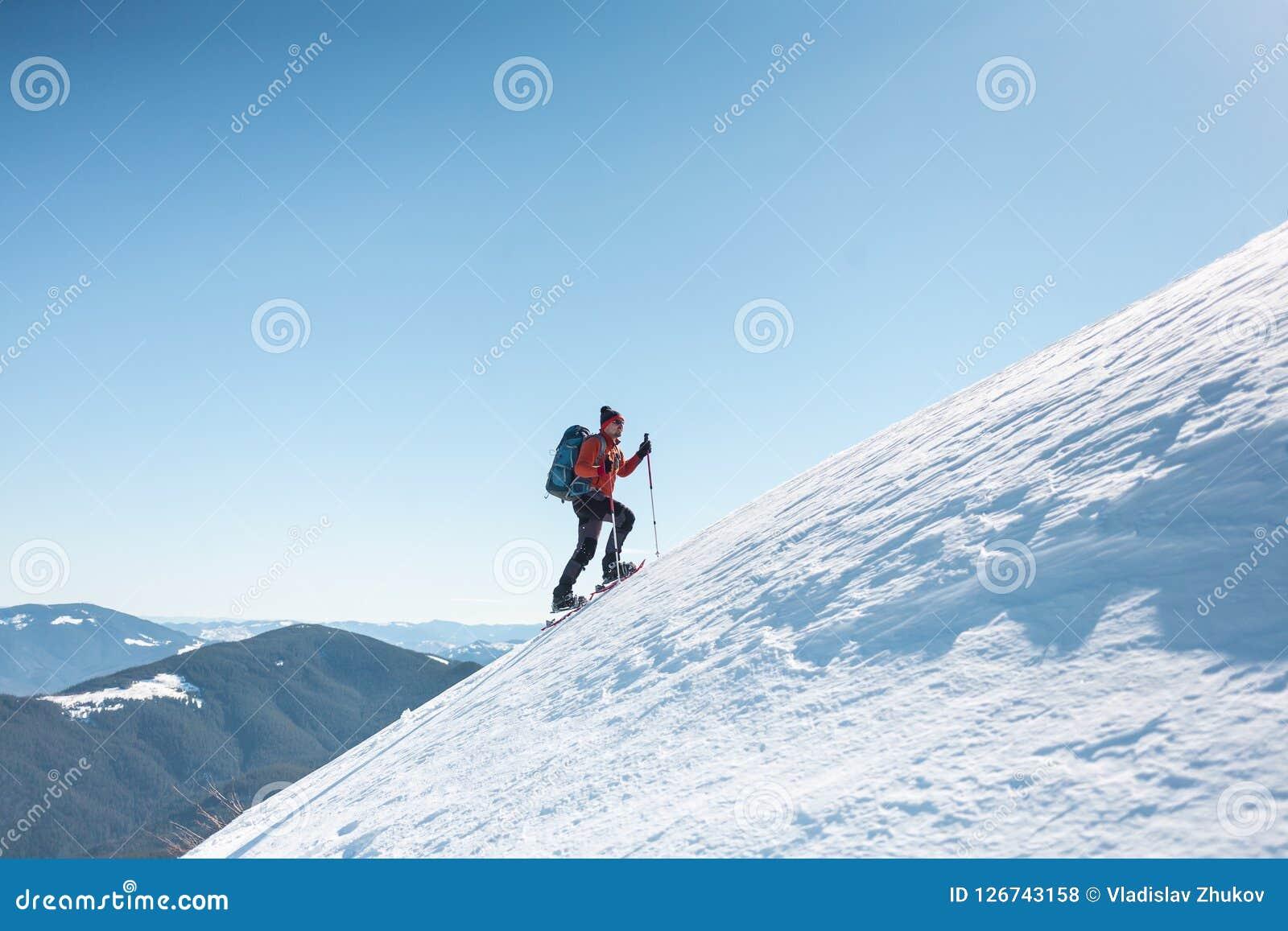 Een mens beklimt tot de bovenkant van de berg