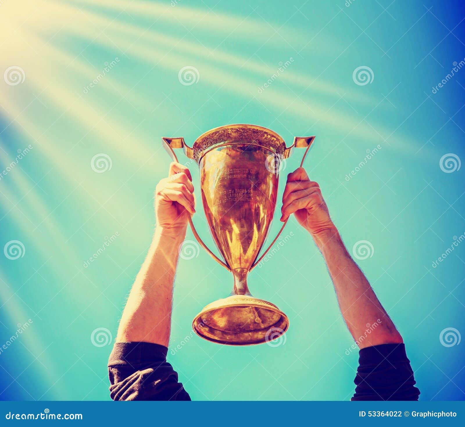 Een mens die een gouden trofeekop steunen als winnaar in de concurrentie