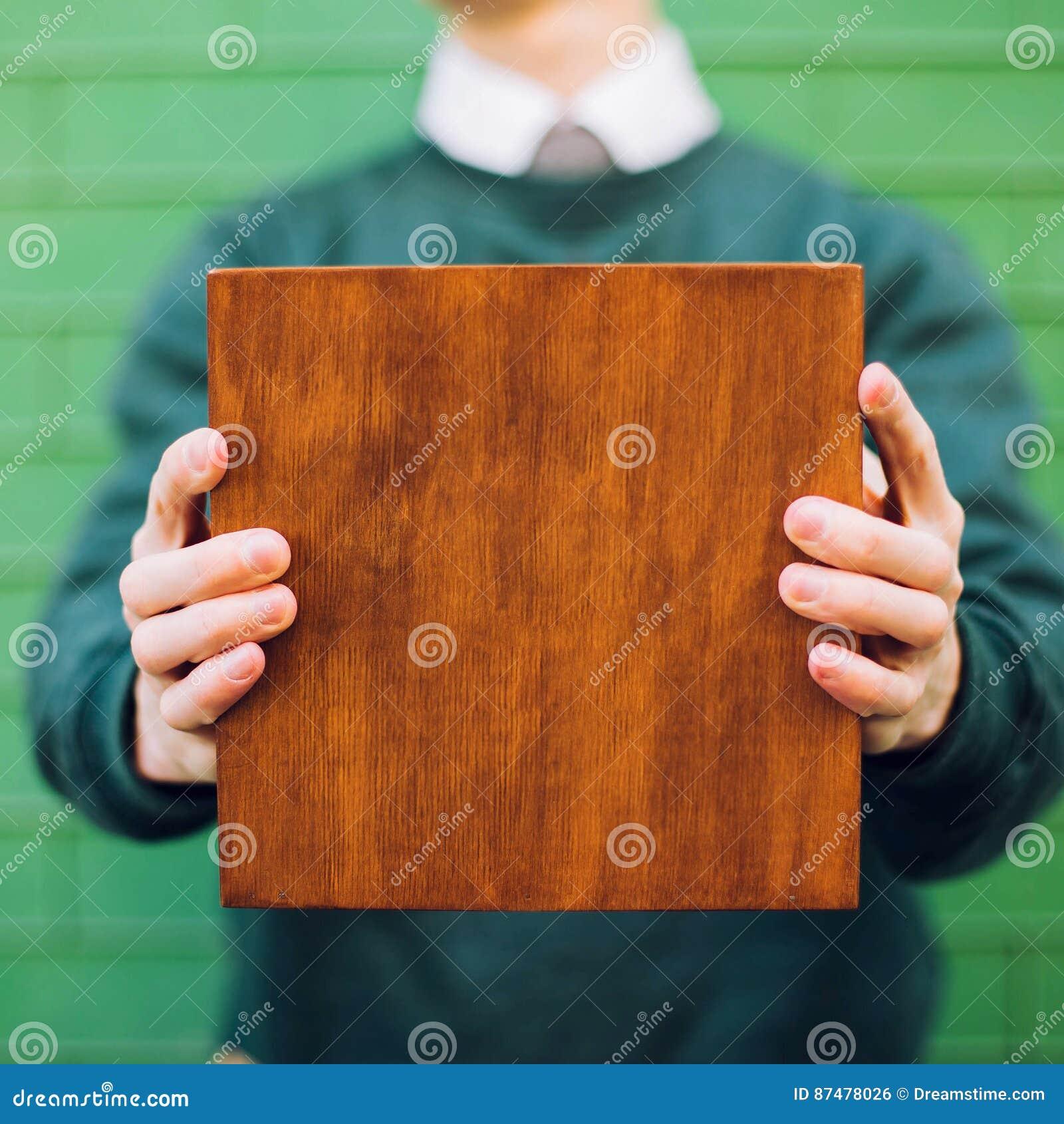 Een mens die een houten doos houden
