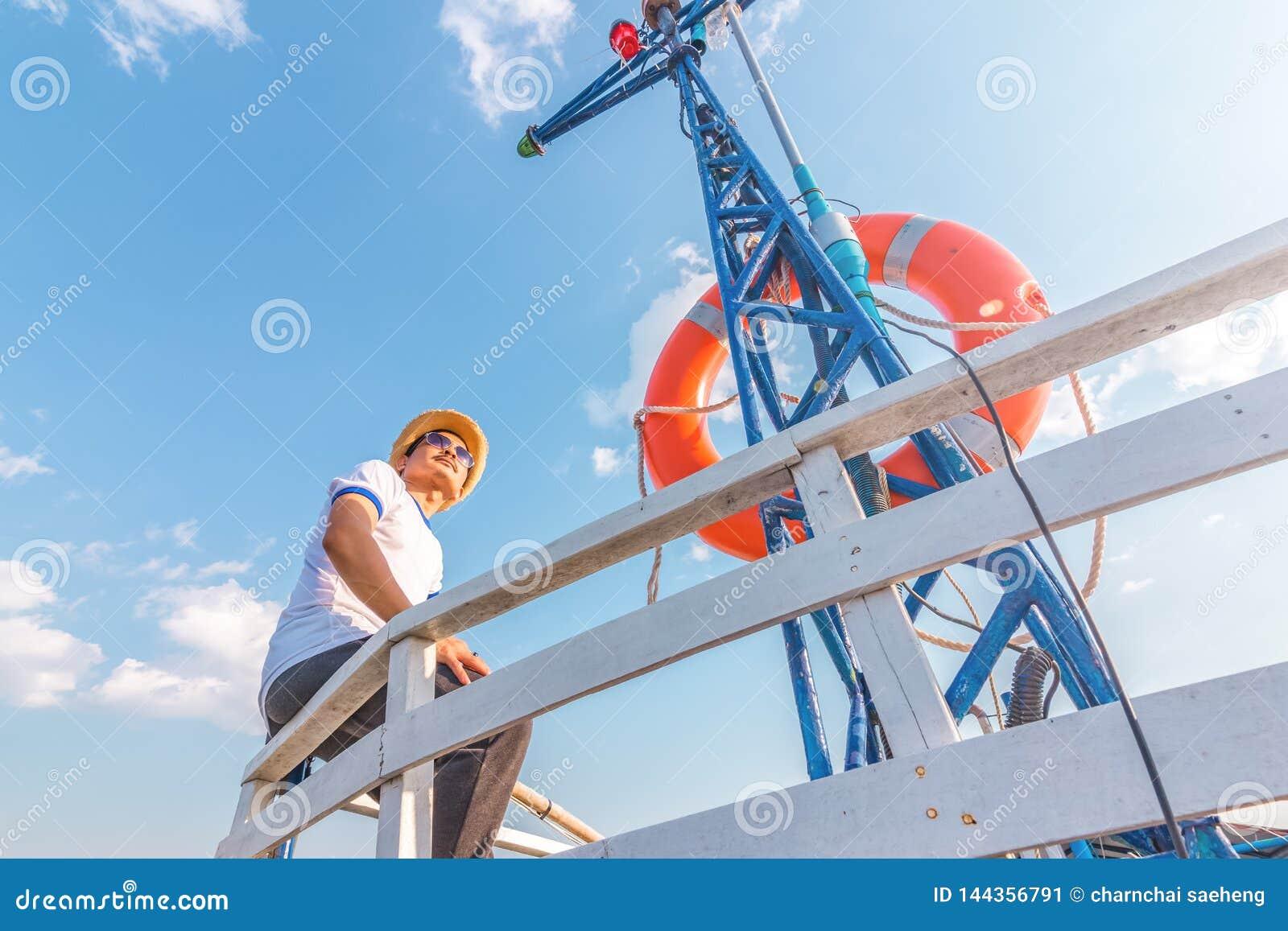 Een mens die gelukkig op het jacht ontspannen die van de vakantiezeilboot een rust op de zomerboot en blauwe hemelachtergrond heb