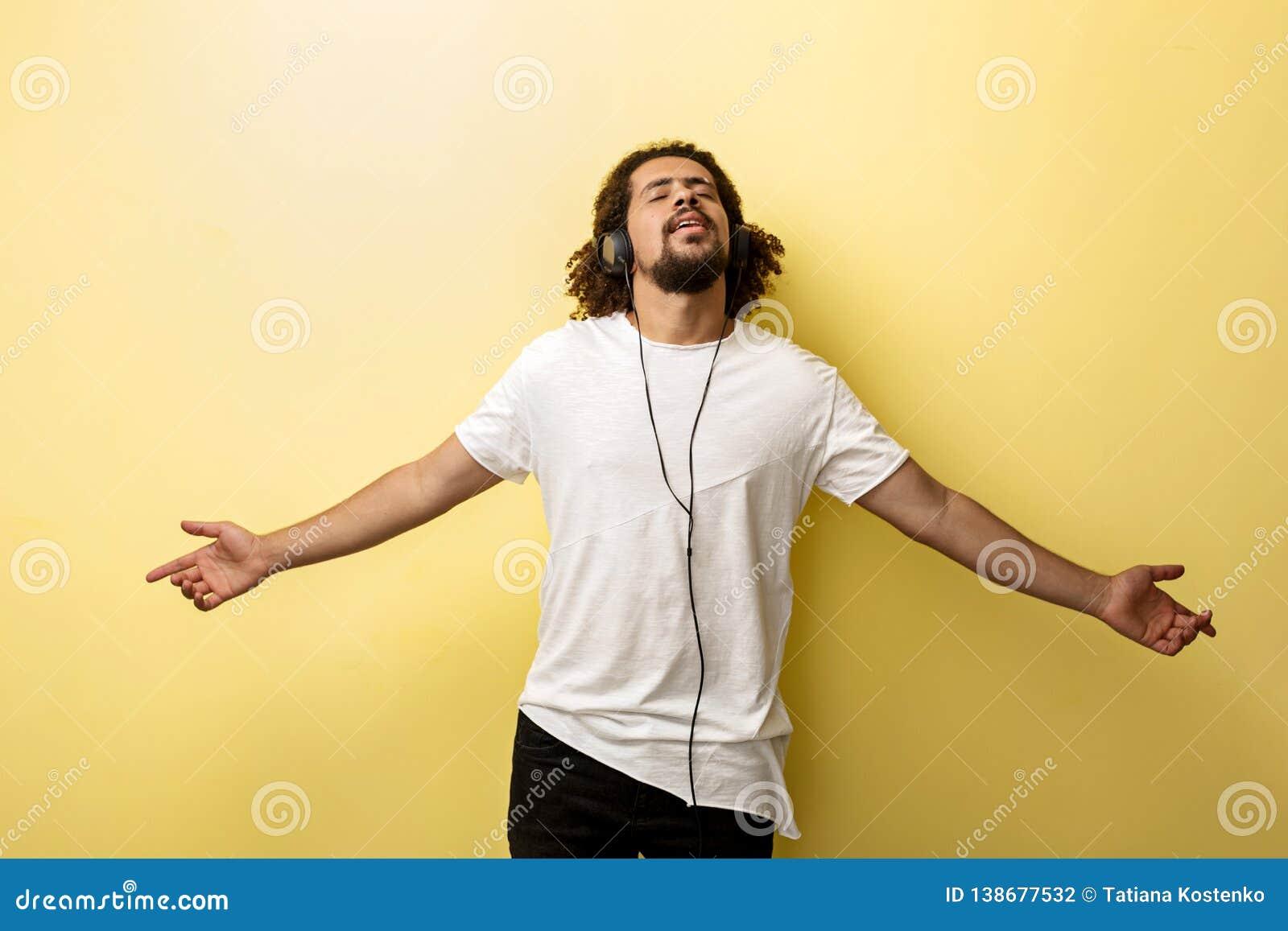 Een mens die hoofdtelefoons in het open lichaamsstandpunt dragen luistert aan muziek met een zaligheiduitdrukking op het gezicht