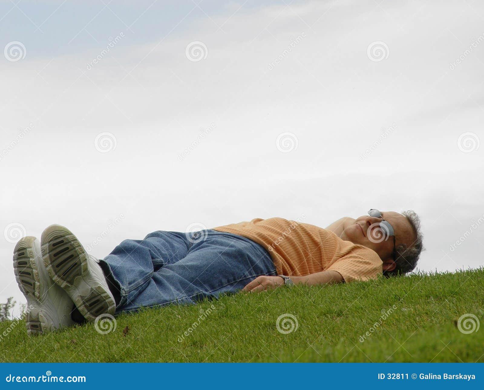 Een mens die op het gras ligt