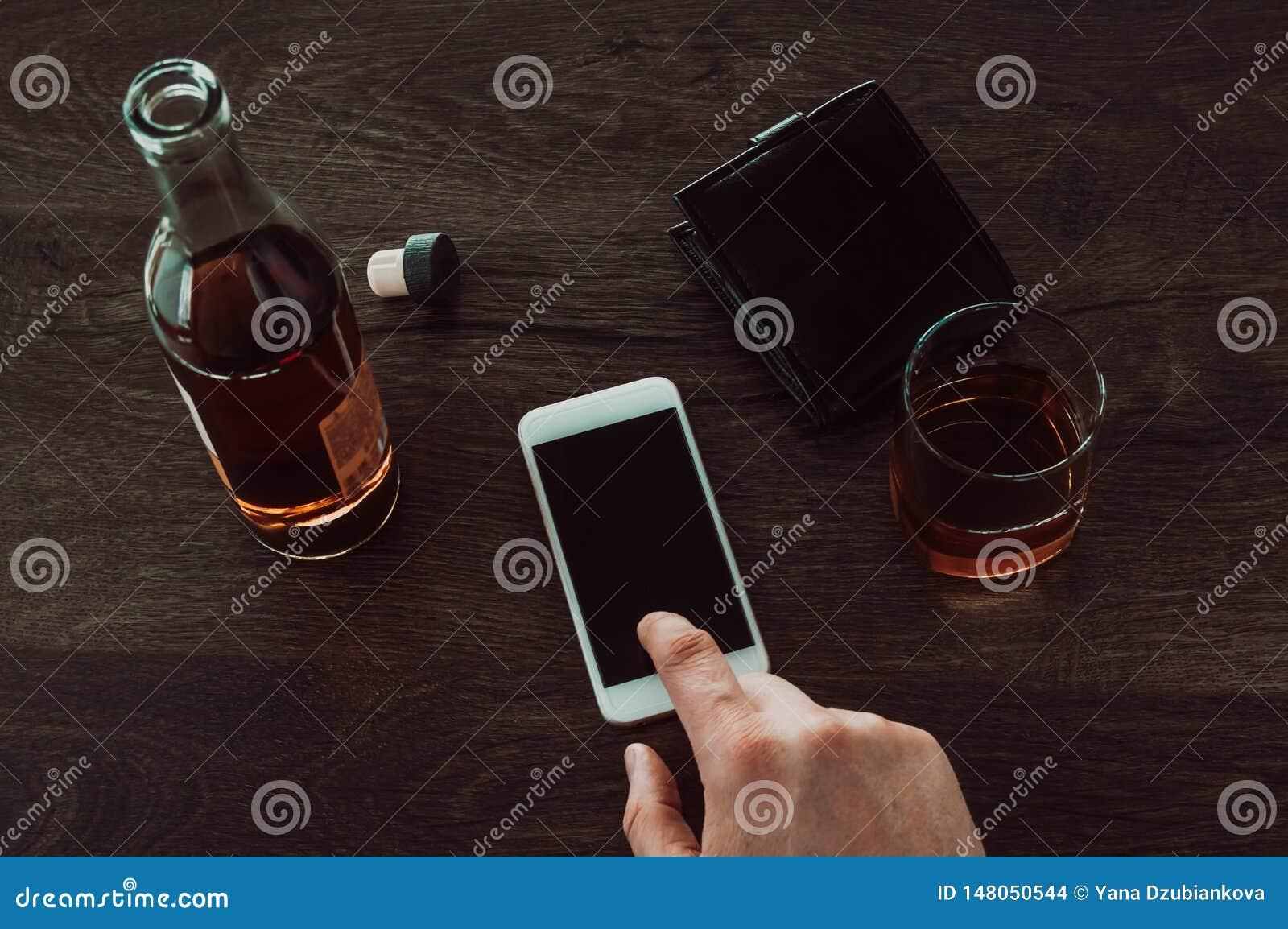 Een mens drukt een vinger op een mobiele telefoon Daarna op de lijst is een glas whisky, een fles whisky en een beurs